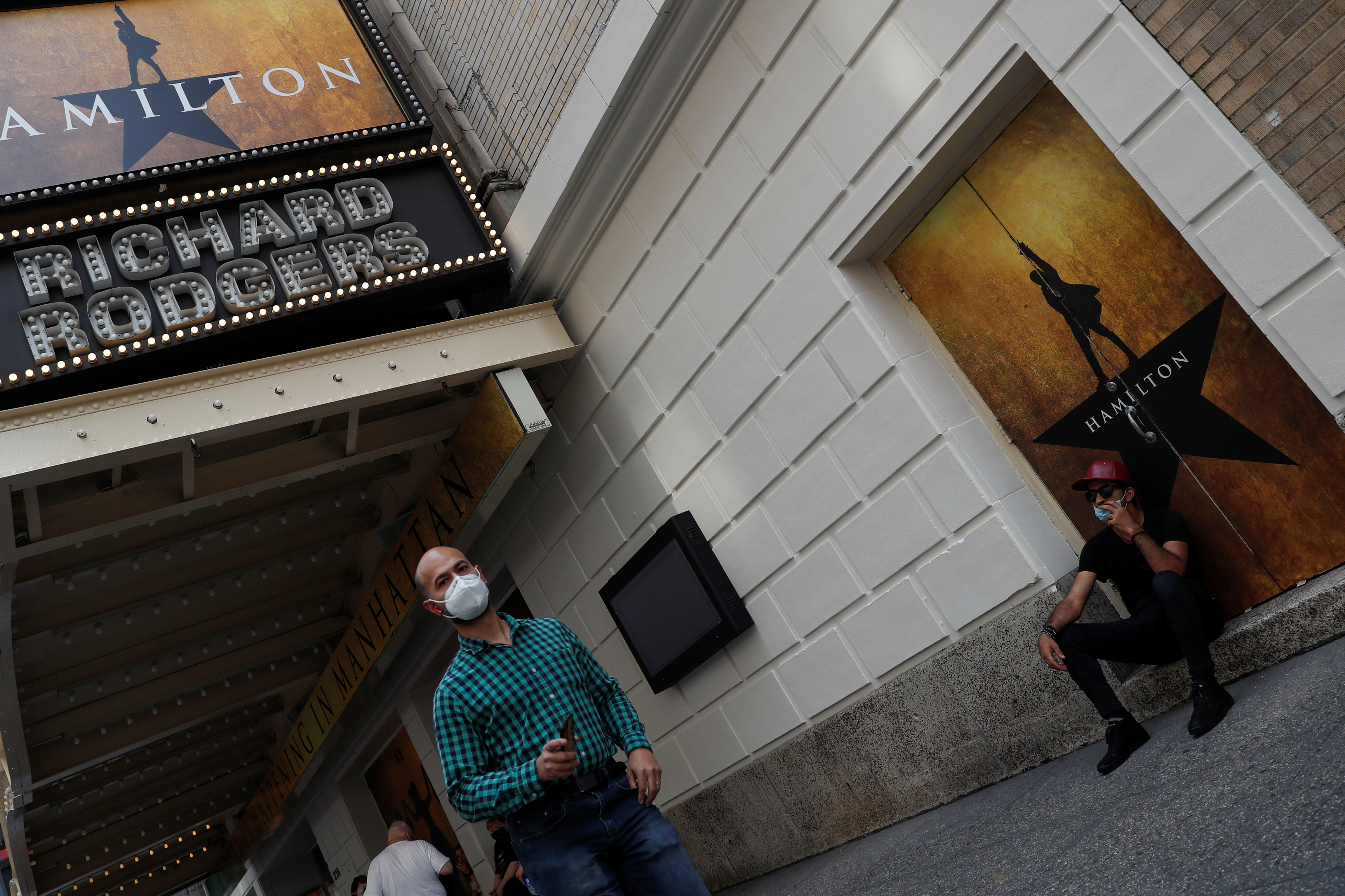 """A man walks wearing a protective face mask past the marquee for the Broadway show """"Hamilton"""" in the Times Square area of Manhattan, New York City, U.S., September 14, 2021.  REUTERS/Shannon Stapleton"""