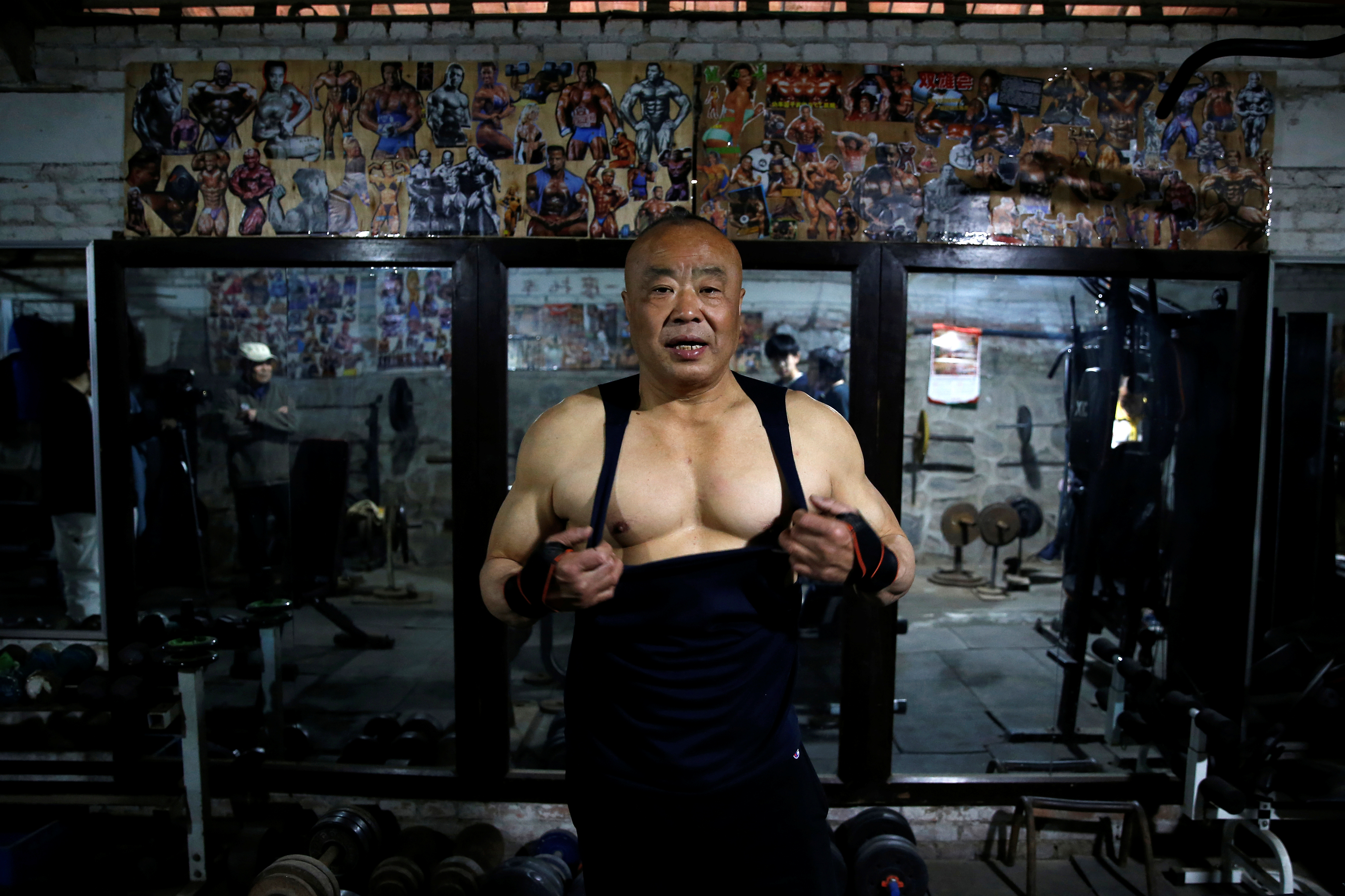 Xu Wei, a 63-year-old former factory worker and the current gym manager, show his muscles at the gym which has been turned from a bicycle shed inside a residential compound in the southwest of Beijing, China April 8, 2021. REUTERS/Tingshu Wang
