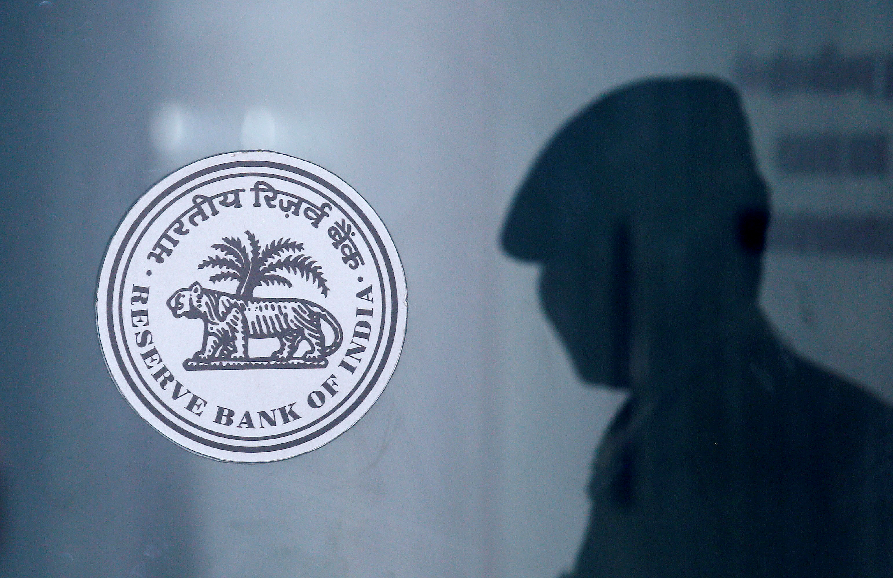 A security guard's reflection is seen next to the logo of the Reserve Bank Of India (RBI) at the RBI headquarters in Mumbai, India, June 6, 2019. REUTERS/Francis Mascarenhas/File Photo