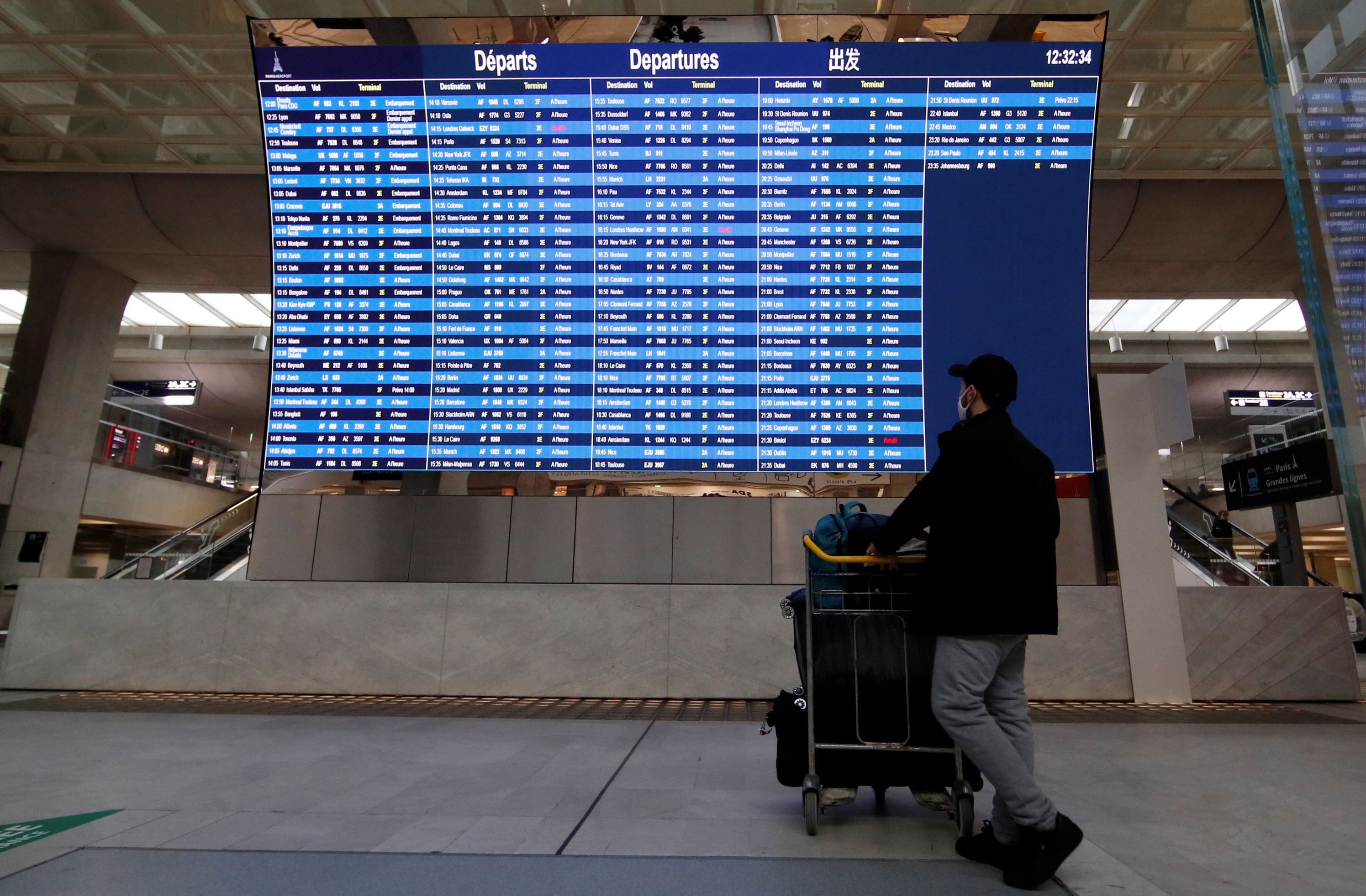 A passenger looks at a departures board with cancelled flights from Paris to London and Bristol at Paris Charles de Gaulle airport in Roissy near Paris, amid the spread of the coronavirus disease (COVID-19) in France, December 21, 2020. REUTERS/Gonzalo Fuentes