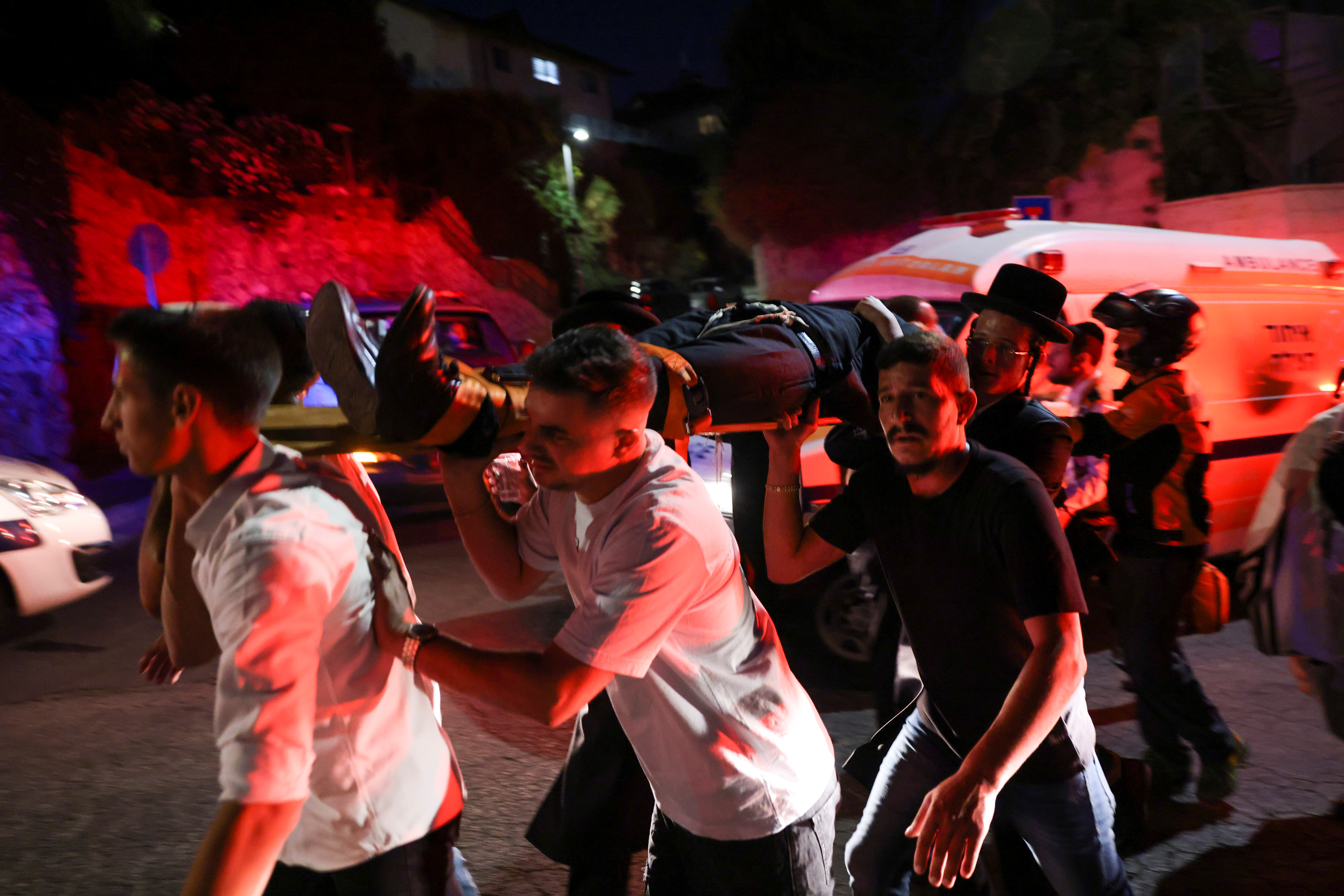 Jewish worshippers and rescue workers carry injured people outside a synagogue where a grandstand collapsed during a religious celebration in Givat Zeev, in the occupied West Bank, May 16, 2021. REUTERS/Ronen Zvulun