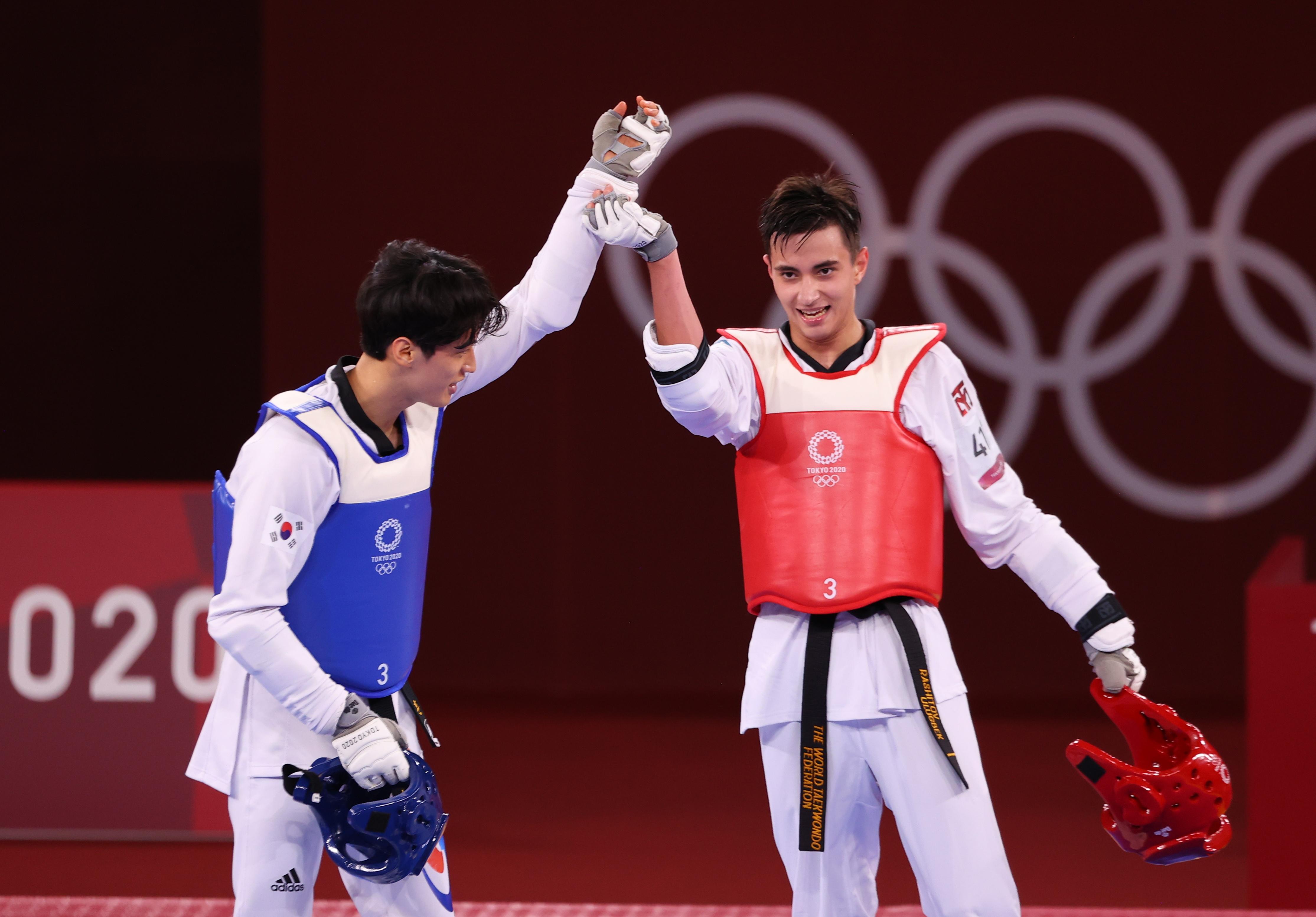 Tokyo 2020 Olympics - Taekwondo - Men's Featherweight 58-68kg - Last 16 - Makuhari Messe Hall A, Chiba, Japan - July 25, 2021. Ulugbek Rashitov of Uzbekistan and Lee Dae-Hoon of South Korea react after competing REUTERS/Murad Sezer