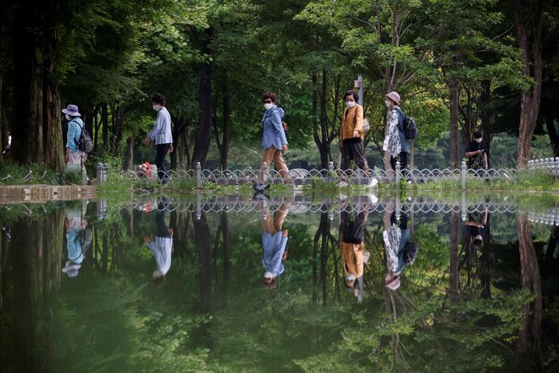 Women wearing masks to avoid contracting the coronavirus disease (COVID-19) take a walk at a park in Seoul, South Korea, June 1, 2021.   REUTERS/Kim Hong-Ji