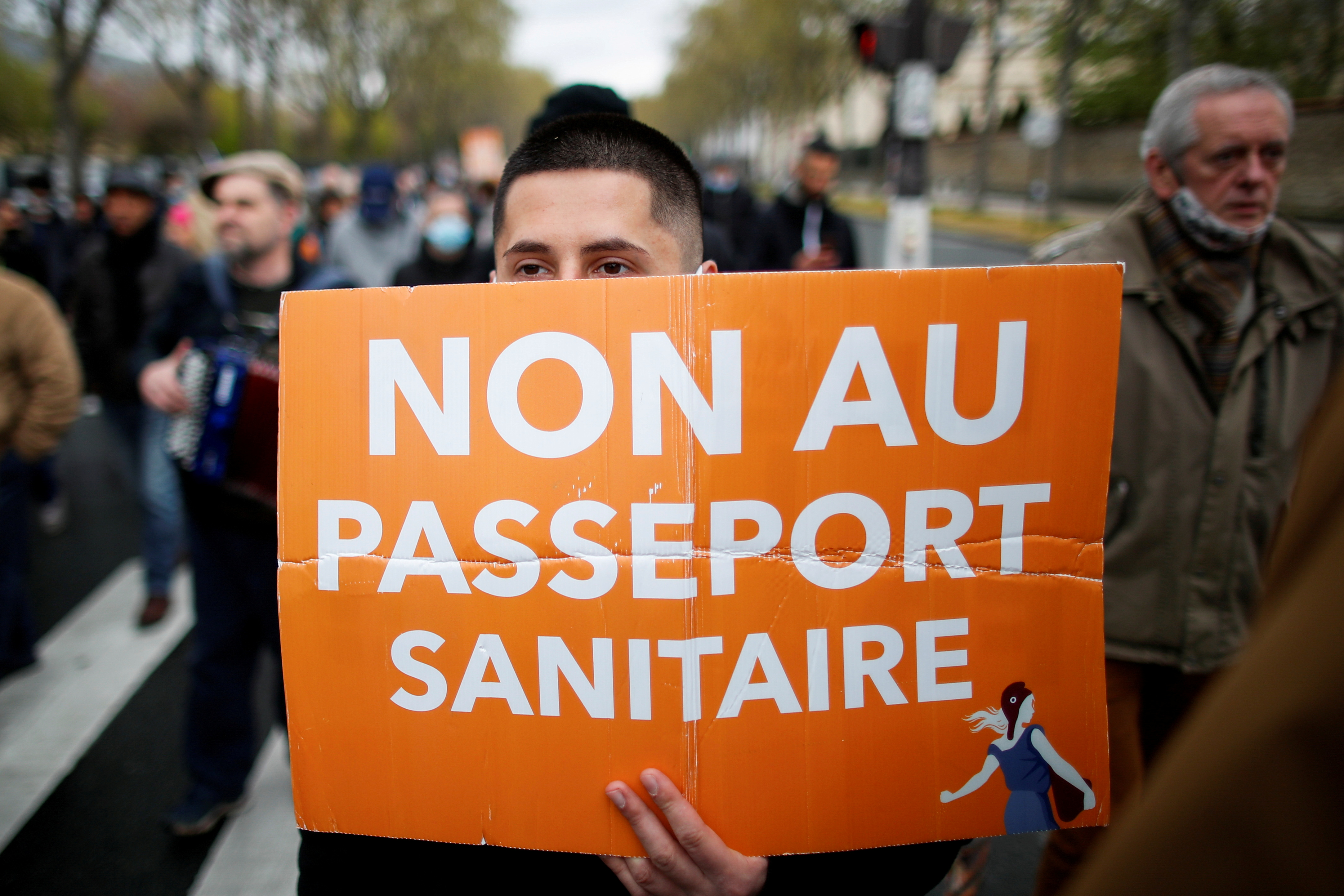 """A supporter of French nationalist party """"Les Patriotes"""" (The Patriots)  holds a placard during a protest against government's economic and social policies during the coronavirus disease (COVID-19) outbreak in Paris, France April 10,2021. The placard reads """"No to the health passport"""". REUTERS/Gonzalo Fuentes/File Photo"""