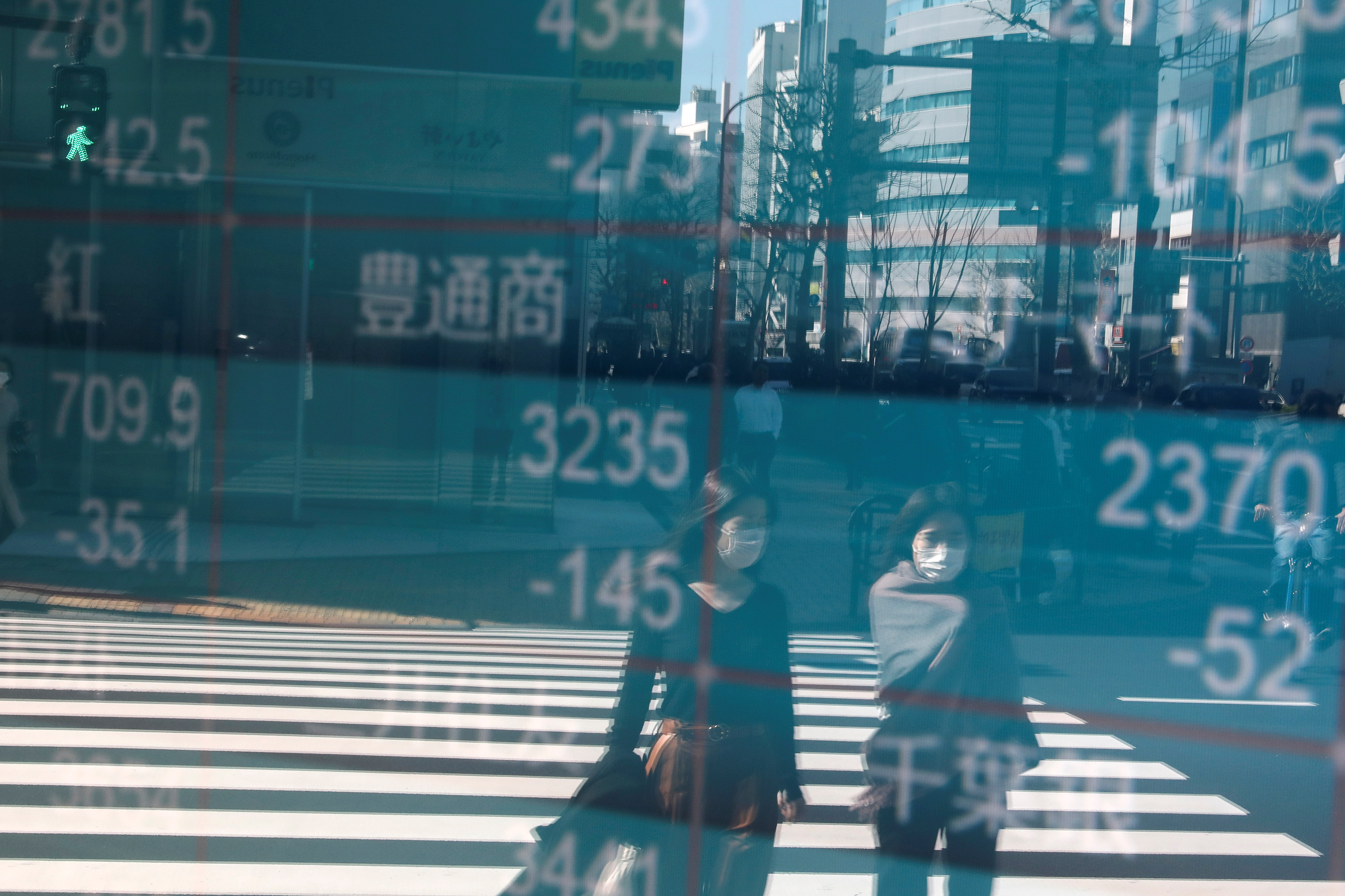 People wearing protective face masks, following an outbreak of the coronavirus, are reflected on a screen showing Nikkei index, outside a brokerage in Tokyo, Japan February 28, 2020. REUTERS/Athit Perawongmetha