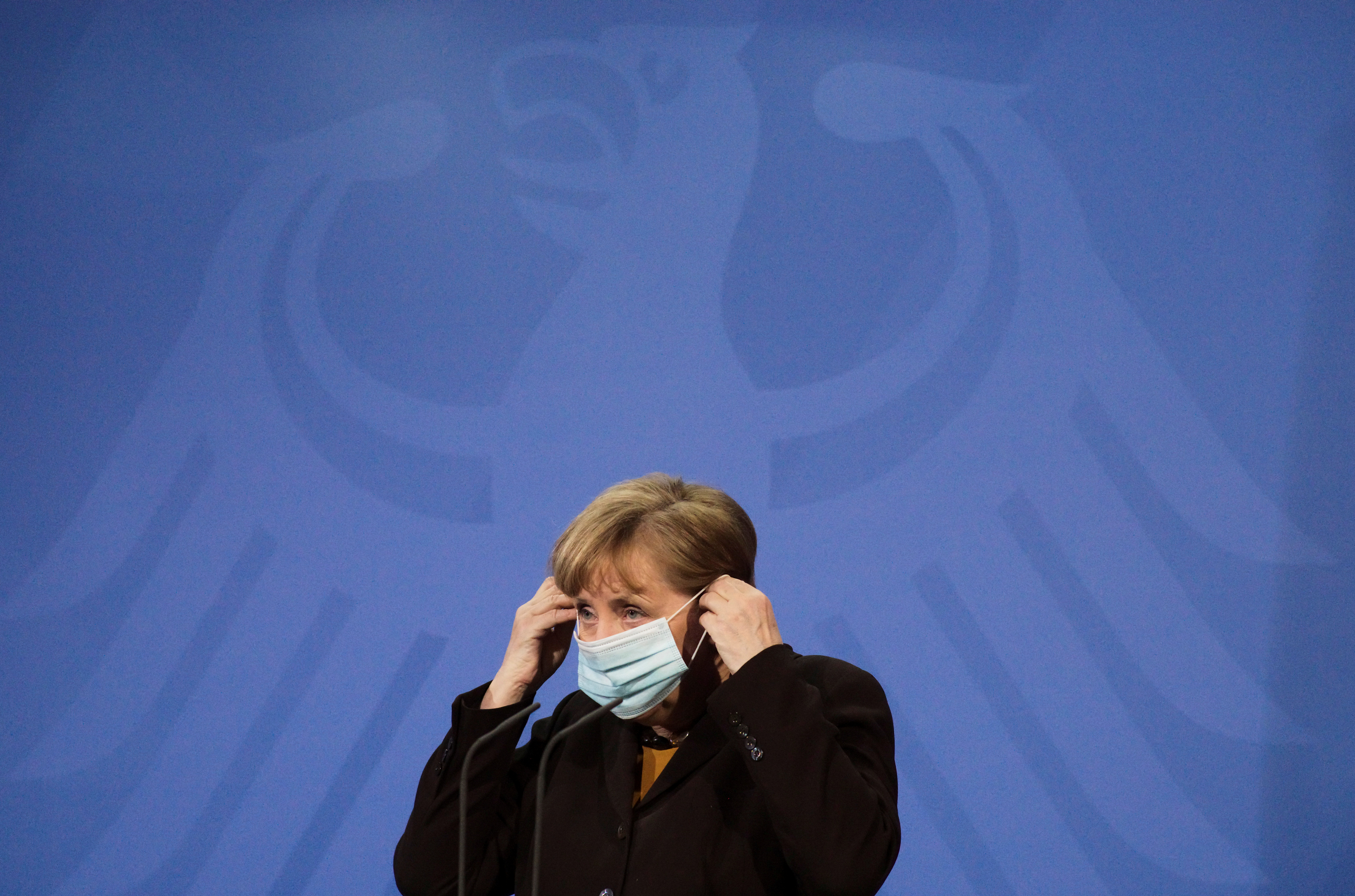 German Chancellor Angela Merkel puts on her face mask as she briefed the media after a virtual meeting with federal state governors at the chancellery in Berlin, Germany, March 30, 2021. Markus Schreiber/Pool via REUTERS