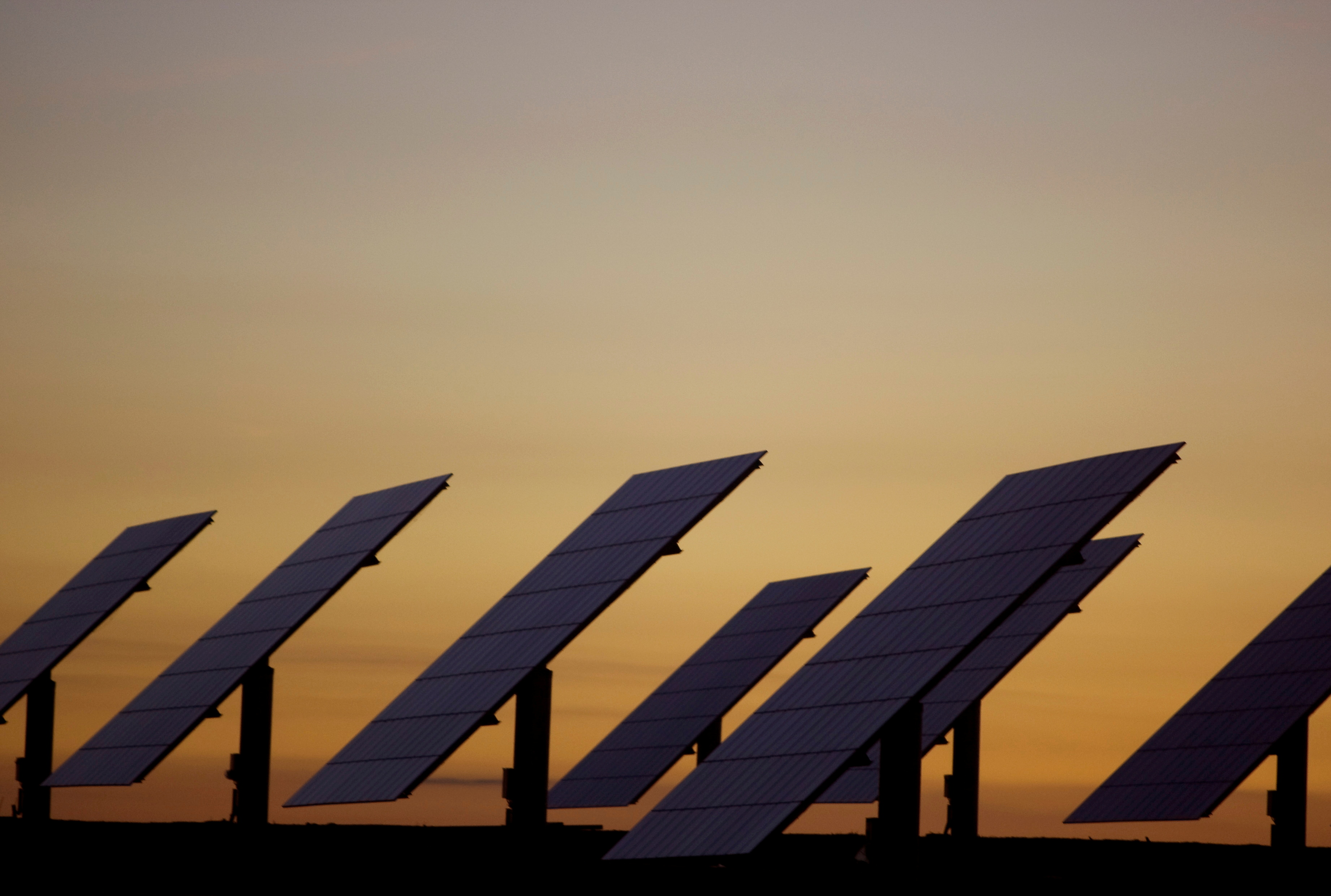 The sun sets beyond solar panels at a power plant in Amareleja, southern Portugal, April 23, 2008. REUTERS/Jose Manuel Ribeiro/File Photo