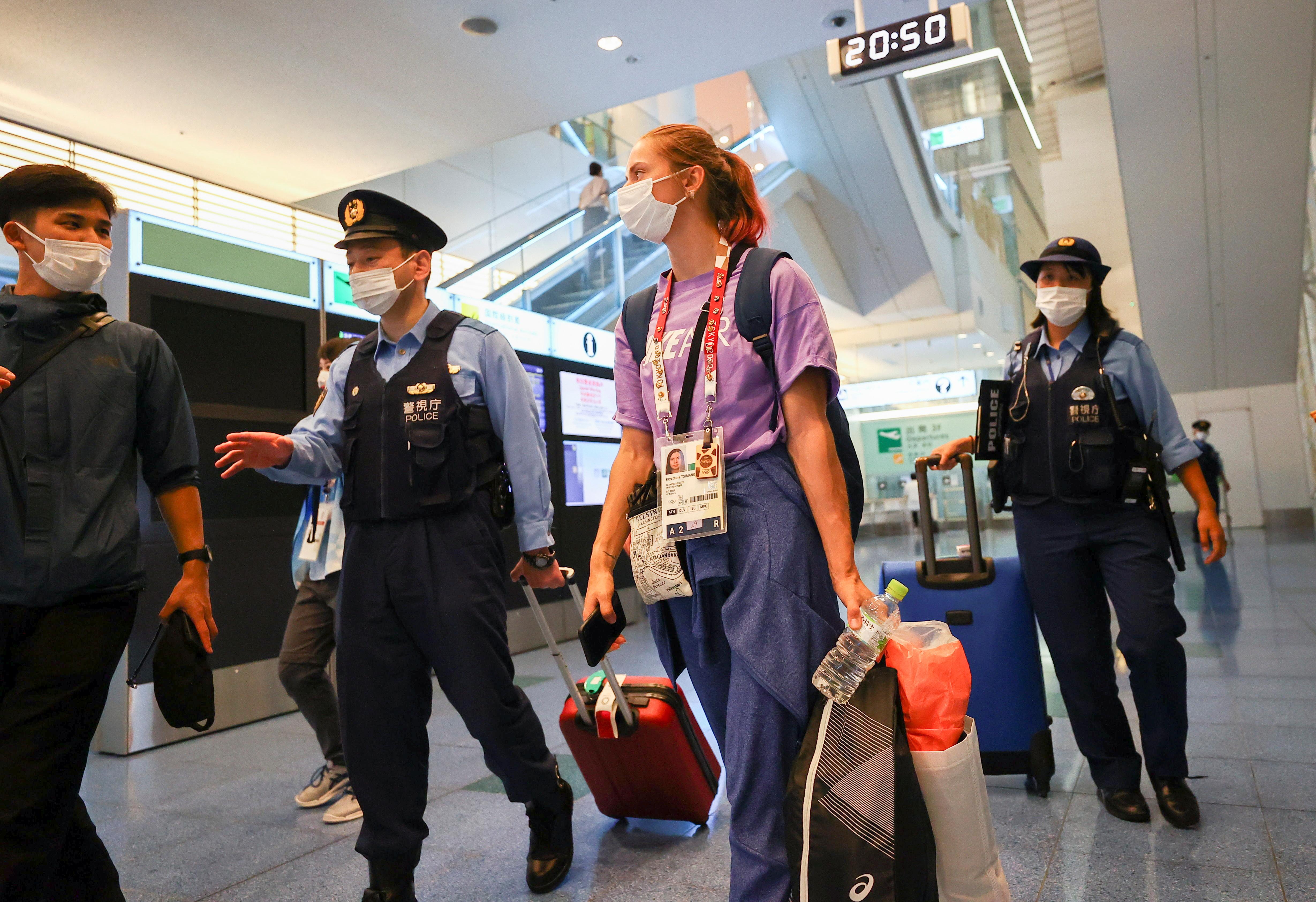Belarusian athlete Krystsina Tsimanouskaya is escorted by police officers at Haneda international airport in Tokyo, Japan August 1, 2021.  REUTERS/Issei Kato