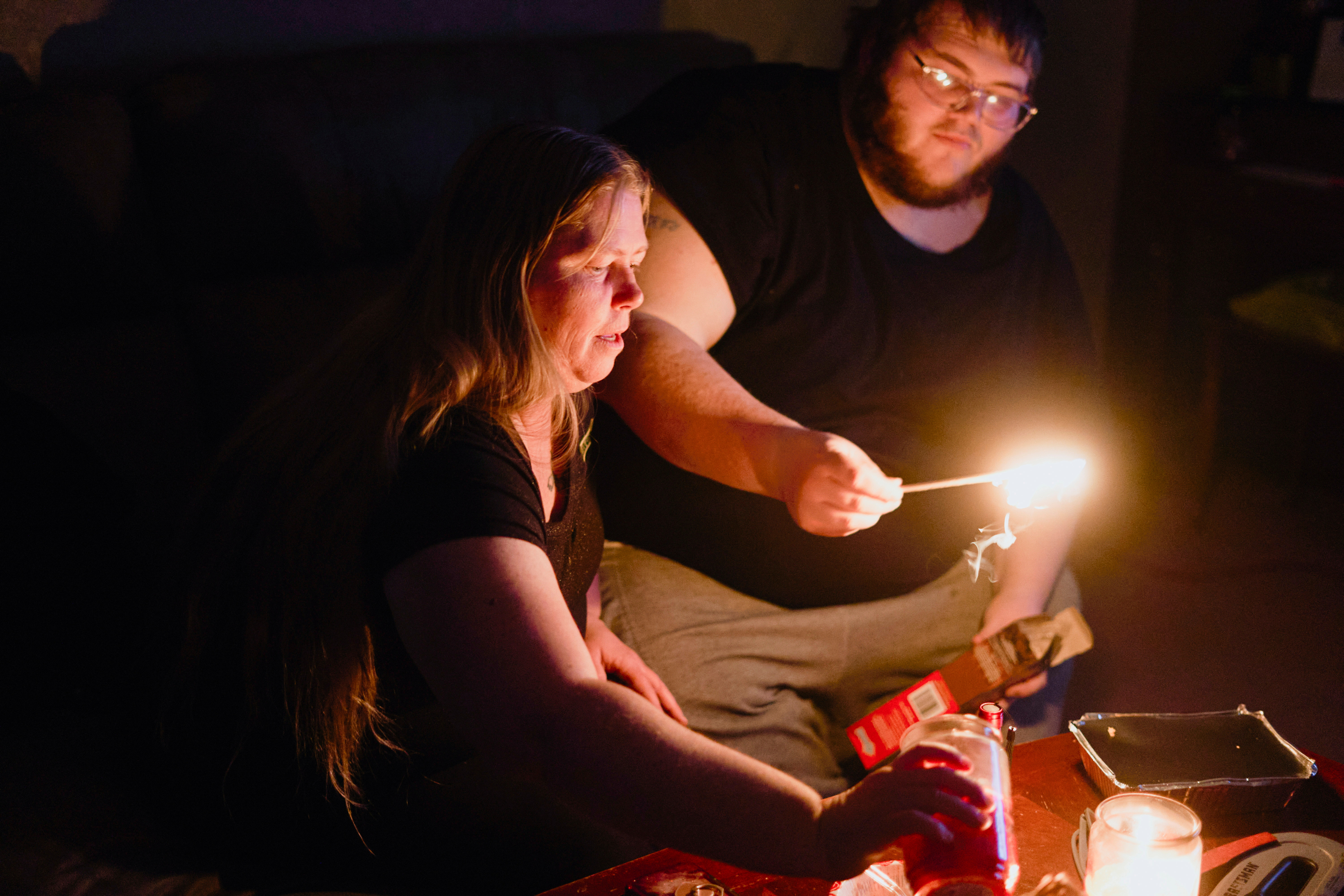 """Christina Beverly and John Shearon light candles in their home after winter weather caused electricity blackouts and """"boil water"""" notices in Fort Worth, Texas, U.S. February 20, 2021. Their home has not had power since blackouts began across the state on Sunday, February 14, 2021, according to the residents.  REUTERS/Cooper Neill/File Photo"""