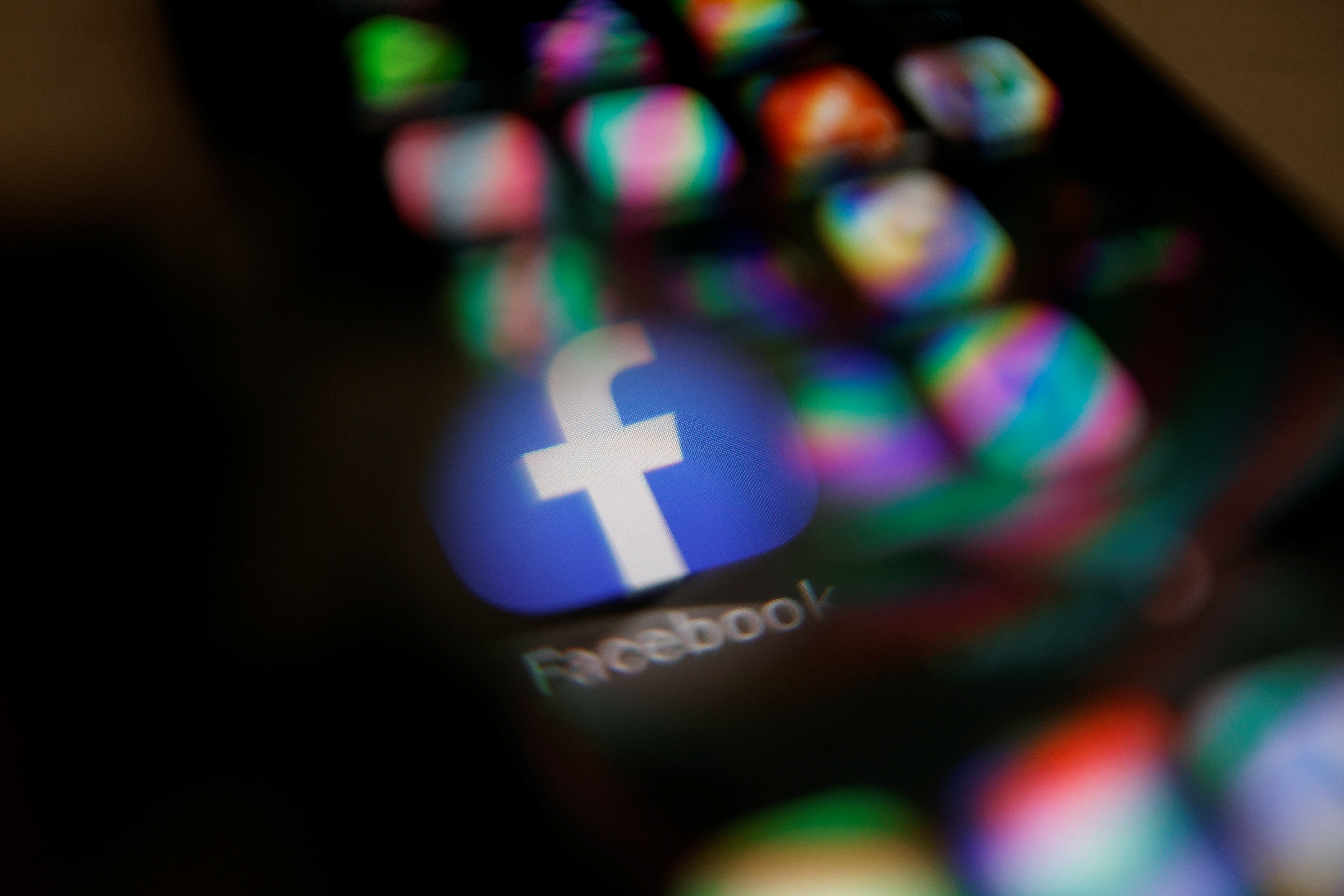 Facebook logo displayed on a mobile phone is seen through a magnifying glass in this picture illustration taken  February 9, 2021. REUTERS/Carlos Jasso