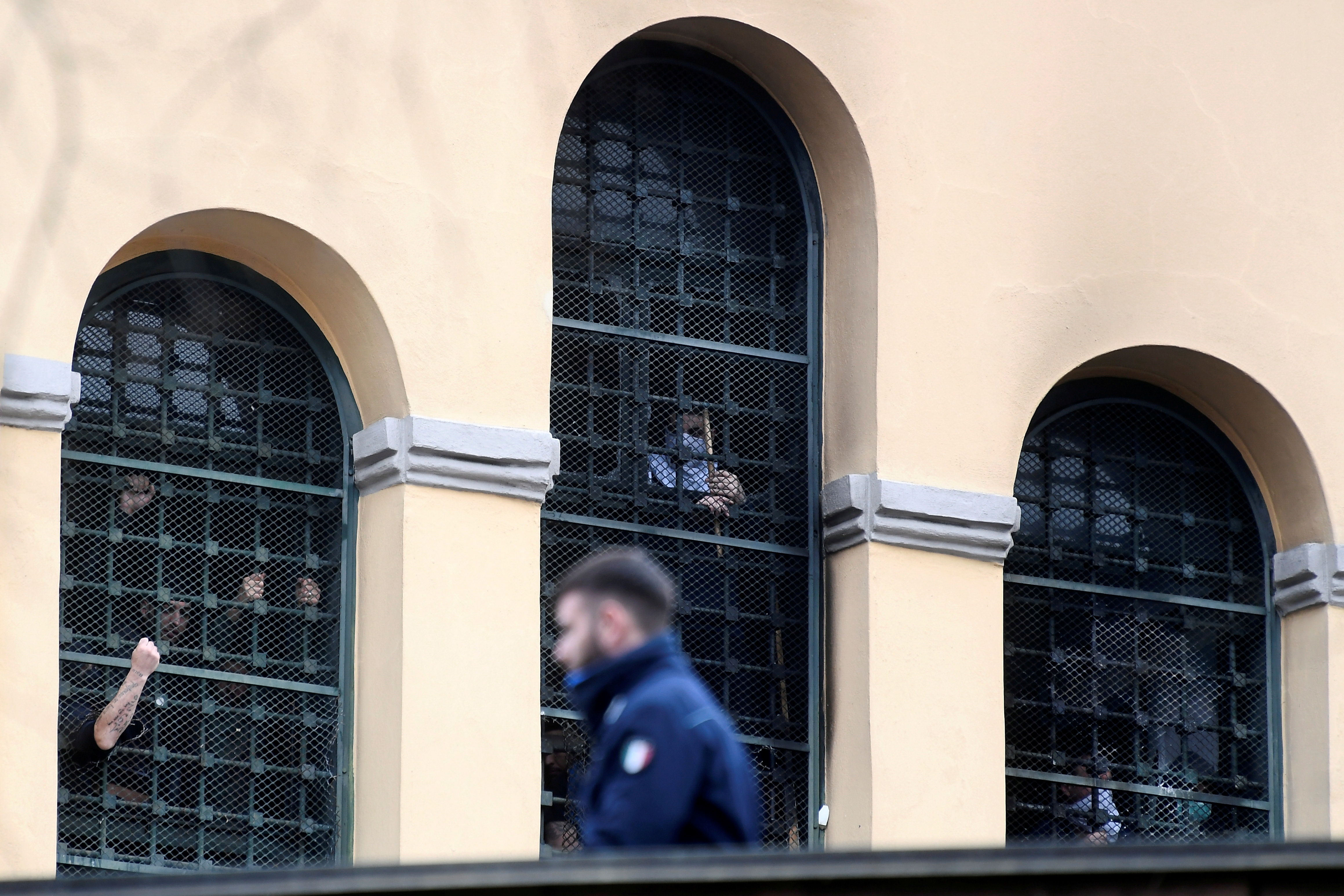 Inmates gather by a barred window during a bout of unrest inside San Vittore Prison in Milan, Italy, March 9, 2020. REUTERS/Flavio Lo Scalzo/File Photo