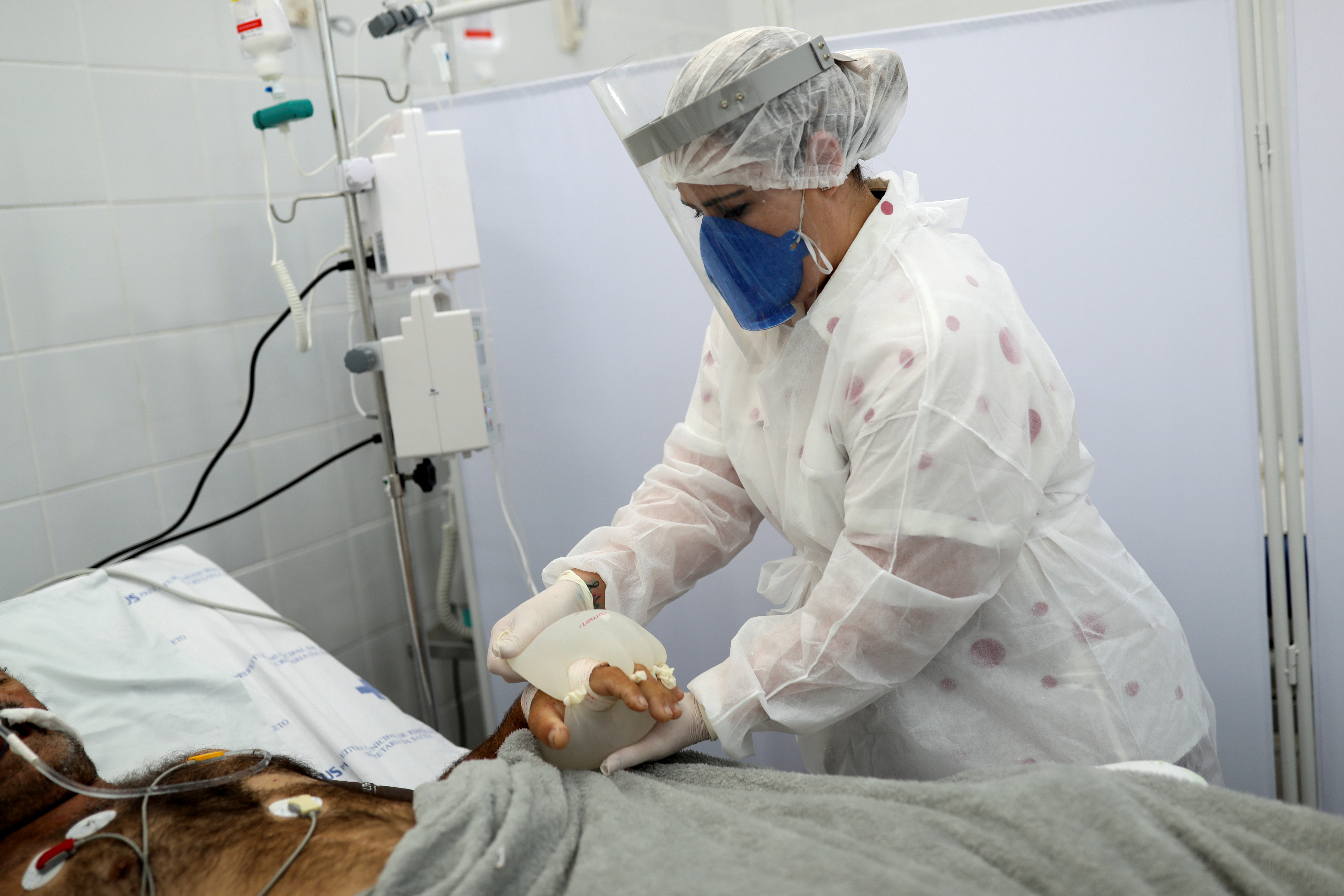 Nurse Vanessa Fermenton puts what she calls 'maozinha do amor' or 'hands of love', warm water-filled gloves, on a coronavirus disease (COVID-19) patient intubated at a UPA (Emergency Service Unit) in Sao Carlos, Sao Paulo state, Brazil April 16, 2021. REUTERS/Amanda Perobelli