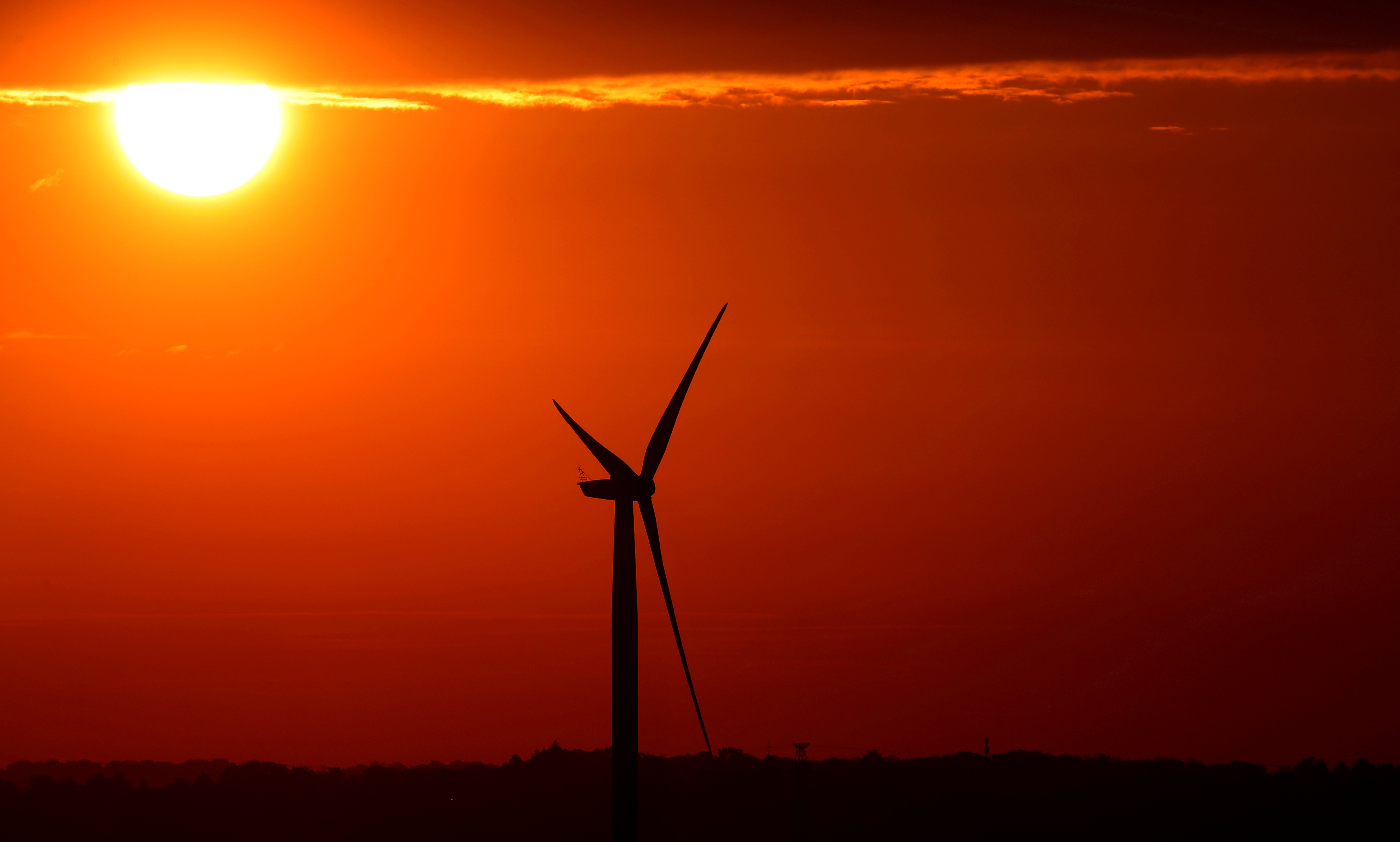 The sun rises behind an electric power windmill in Halle, Belgium September 11, 2019.  REUTERS/Yves Herman