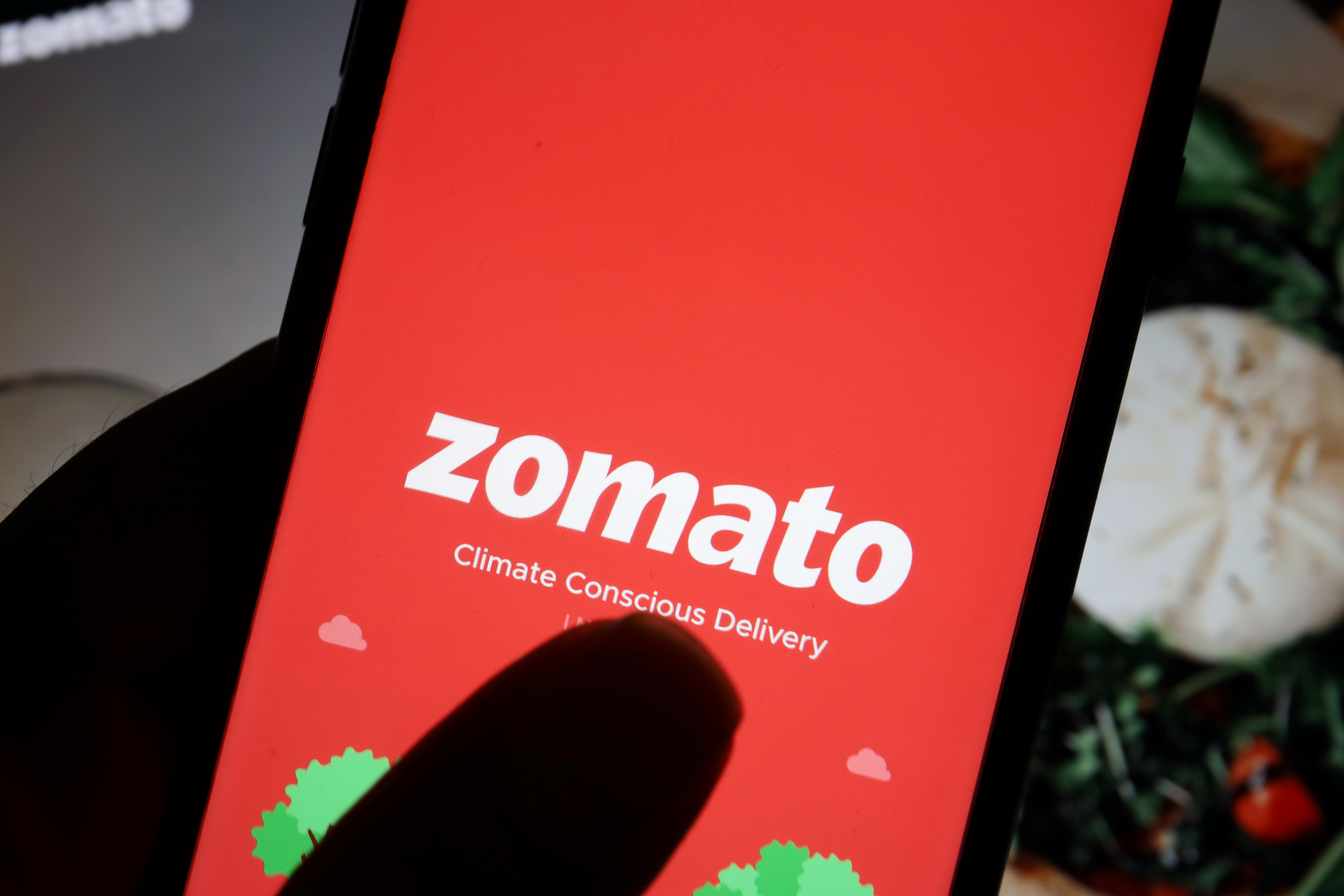 The logo of Indian food delivery company Zomato is seen on its app on a mobile phone displayed in front of its company website in this illustration picture taken July 14, 2021. REUTERS/Florence Lo/Illustration