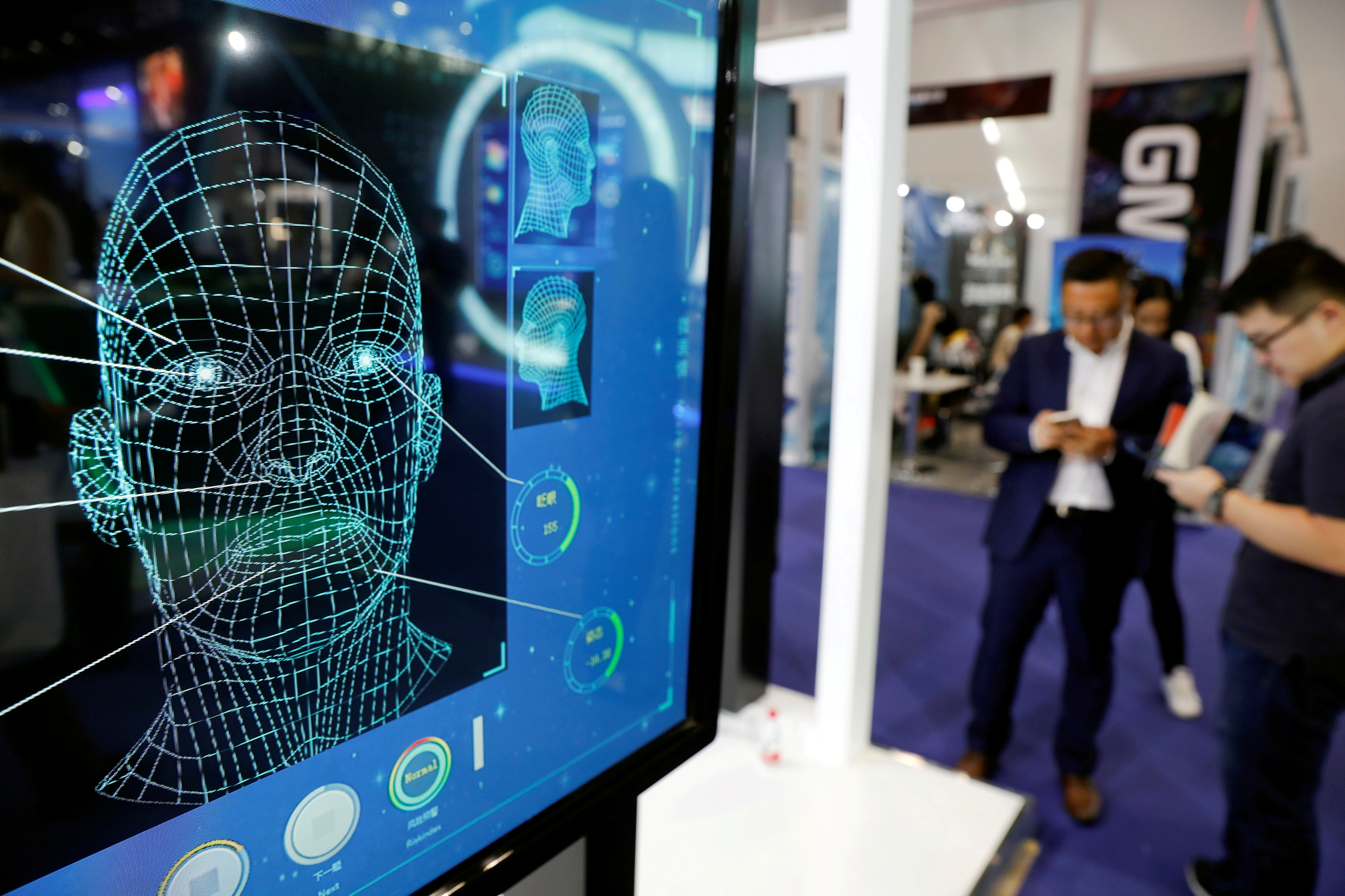 Visitors check their phones behind the screens advertising facial recognition software during Global Mobile Internet Conference at the National Convention in Beijing, China April 27, 2018. REUTERS/Damir Sagolj