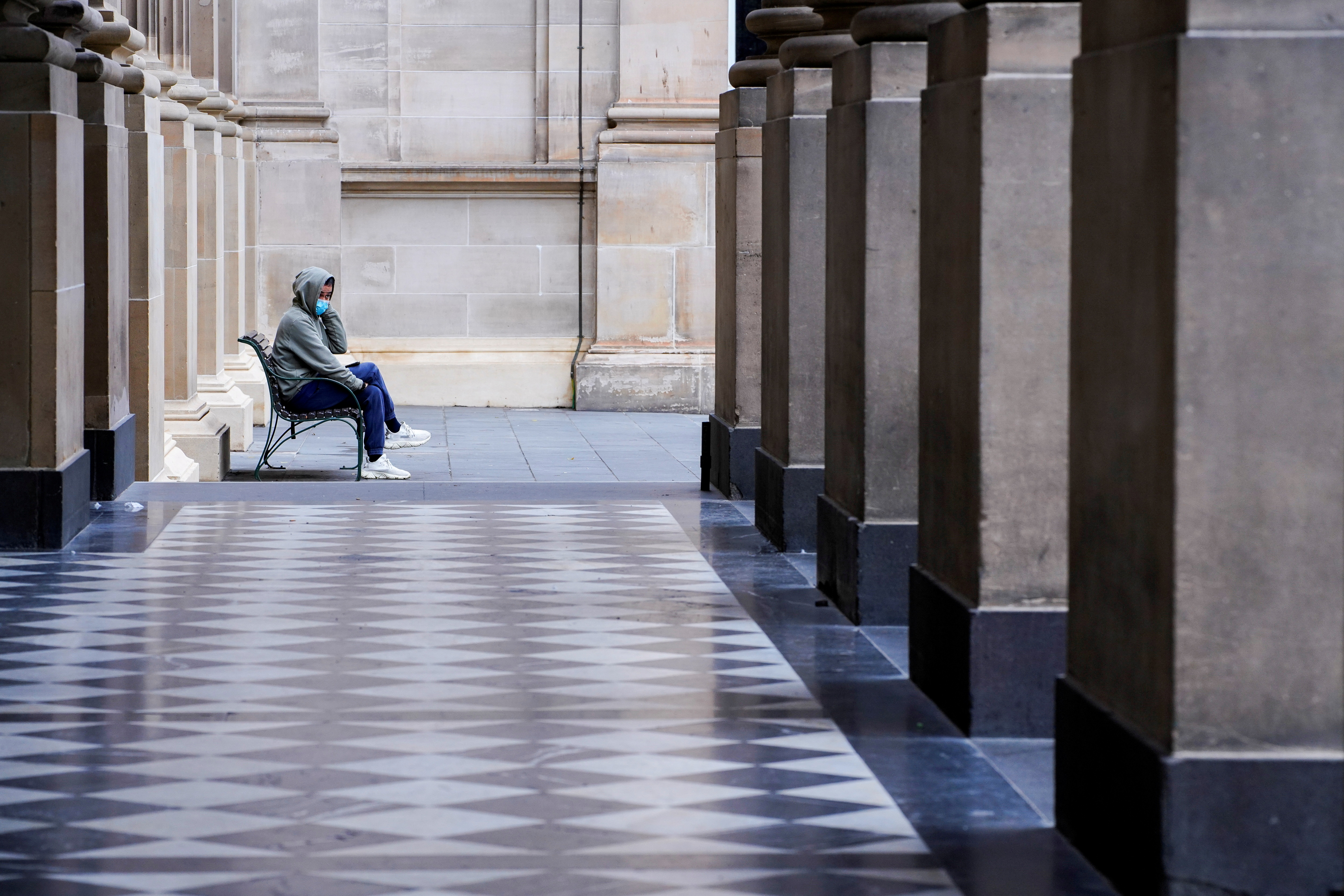 A lone man wearing a protective face mask sits at an unusually quiet State Library as the state of Victoria looks to curb the spread of a coronavirus disease (COVID-19) outbreak in Melbourne, Australia, July 16, 2021.  REUTERS/Sandra Sanders
