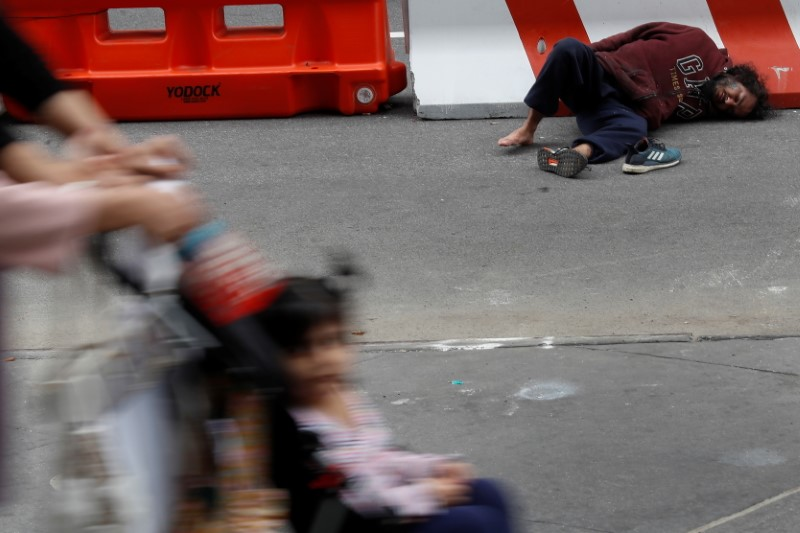 A man lays on the street outside Pennsylvania Station transit hub in New York City, U.S., June 11, 2021. Picture taken June 11, 2021. REUTERS/Shannon Stapleton