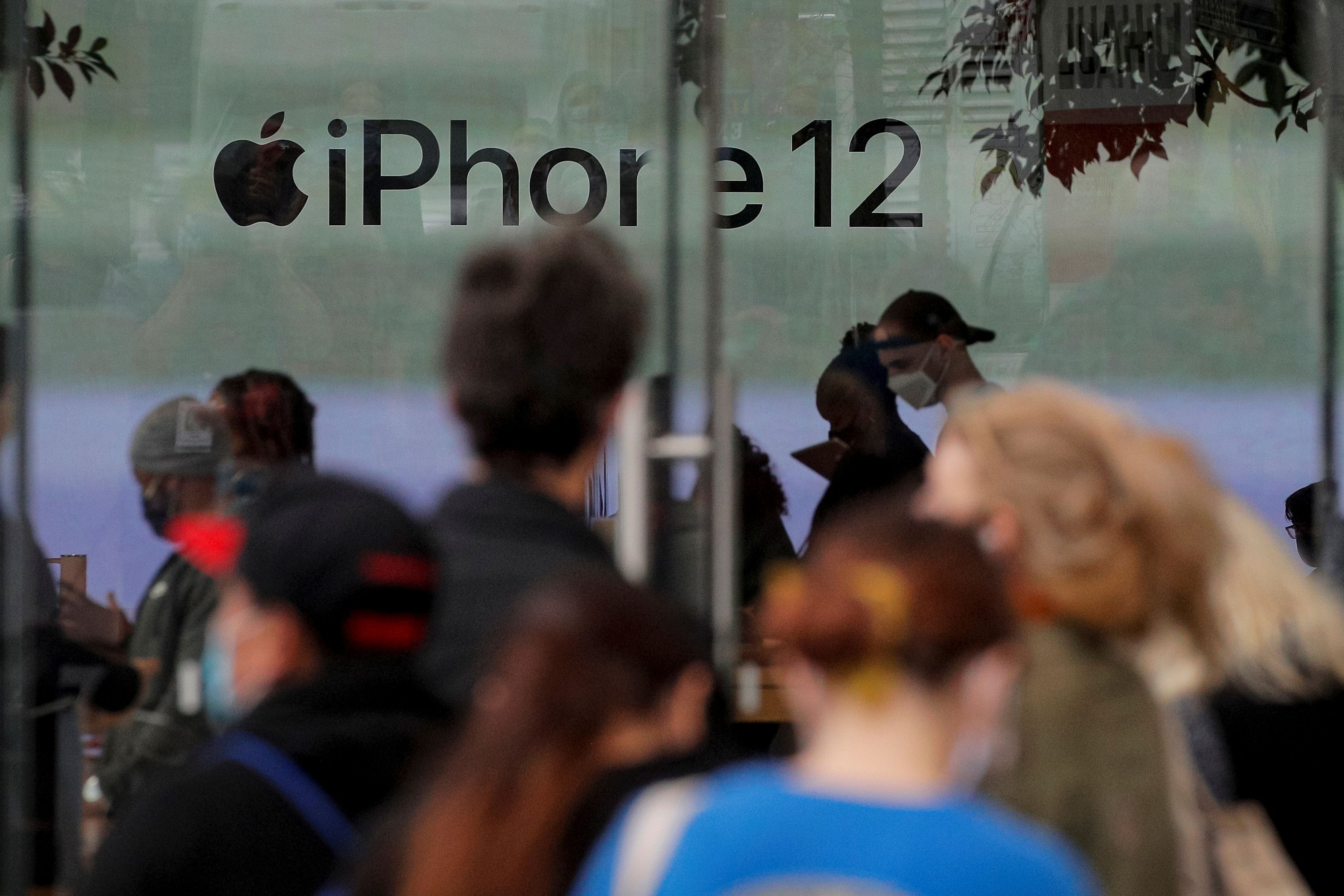 Customers wait in line outside an Apple Store to pick up Apple's new 5G iPhone 12 in Brooklyn, New York, U.S. October 23, 2020.  REUTERS/Brendan McDermid/File Photo
