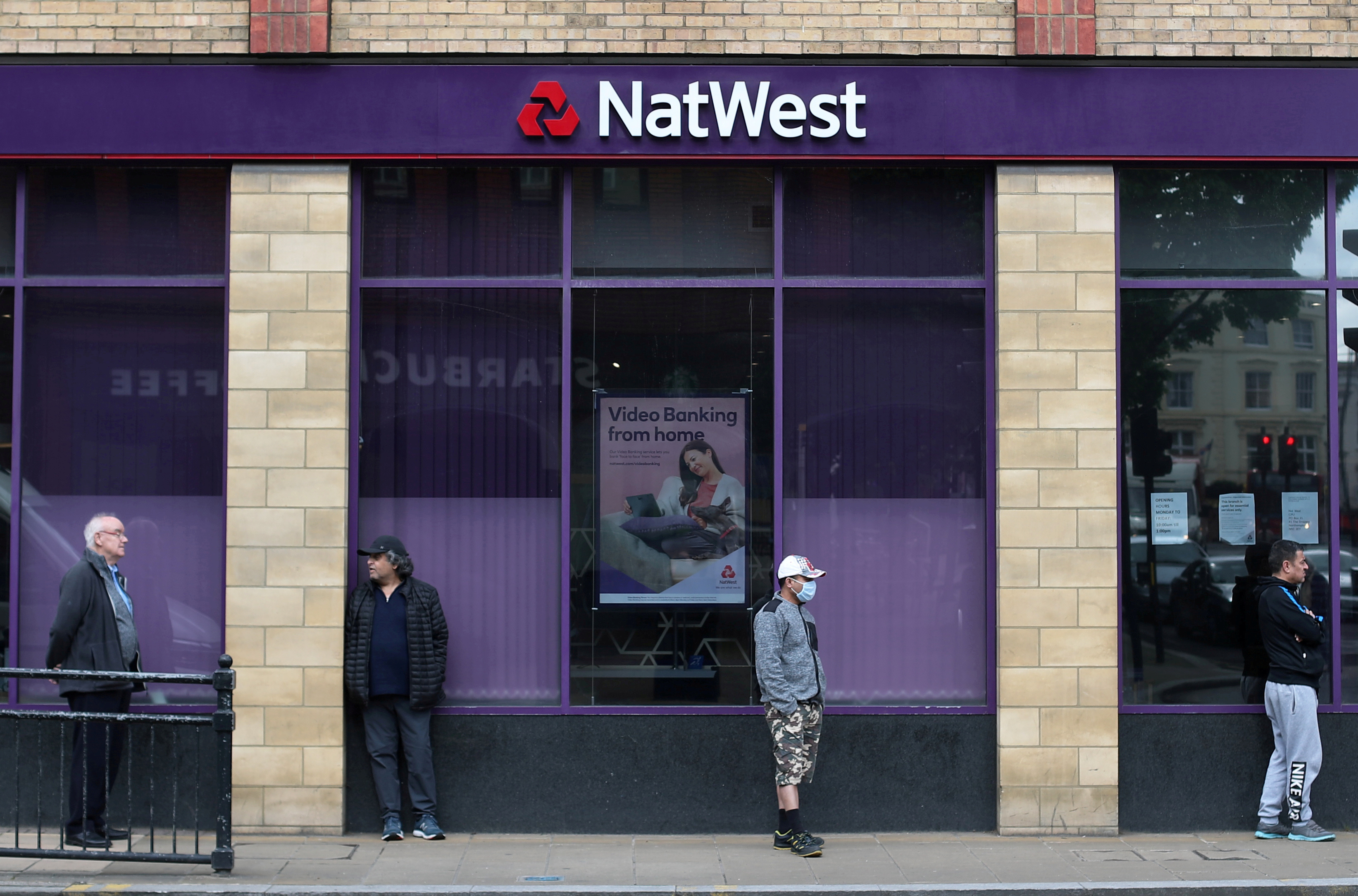 People maintain social distance while they queue outside a Natwest bank in Wimbledon in London, Britain, May 1, 2020. REUTERS/Hannah McKay
