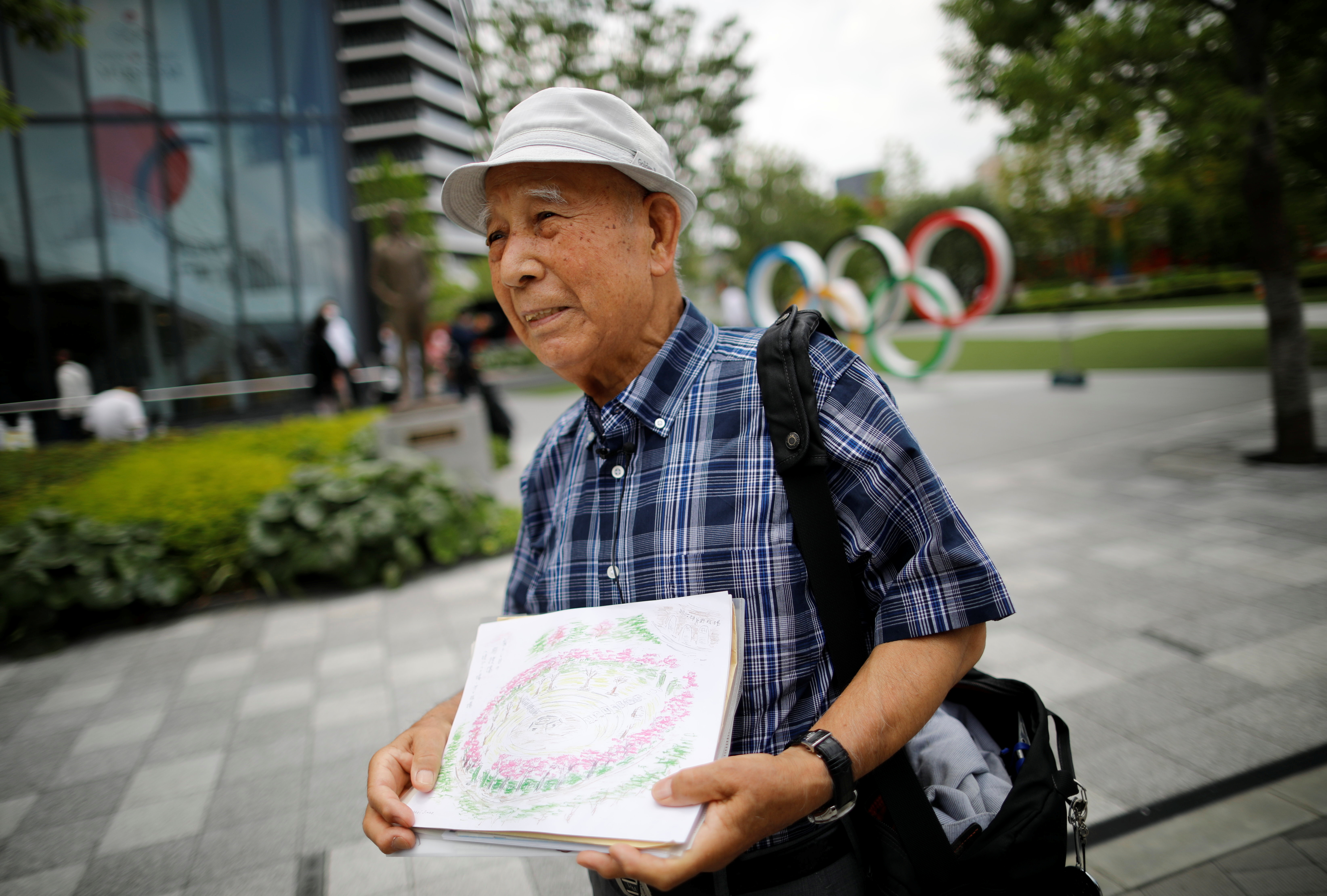 Kohei Jinno, 87, who was forced to leave his house two times ahead of the 1964 and 2020 Olympics Games to make way for construction of the main stadium, speaks in front of the Olympic Rings monument outside the Japan Olympic Museum near the National Stadium, the main stadium for the 2020 Tokyo Olympic Games that have been postponed to 2021 due to the coronavirus disease (COVID-19) pandemic, in Tokyo, Japan June 24, 2021. REUTERS/Issei Kato