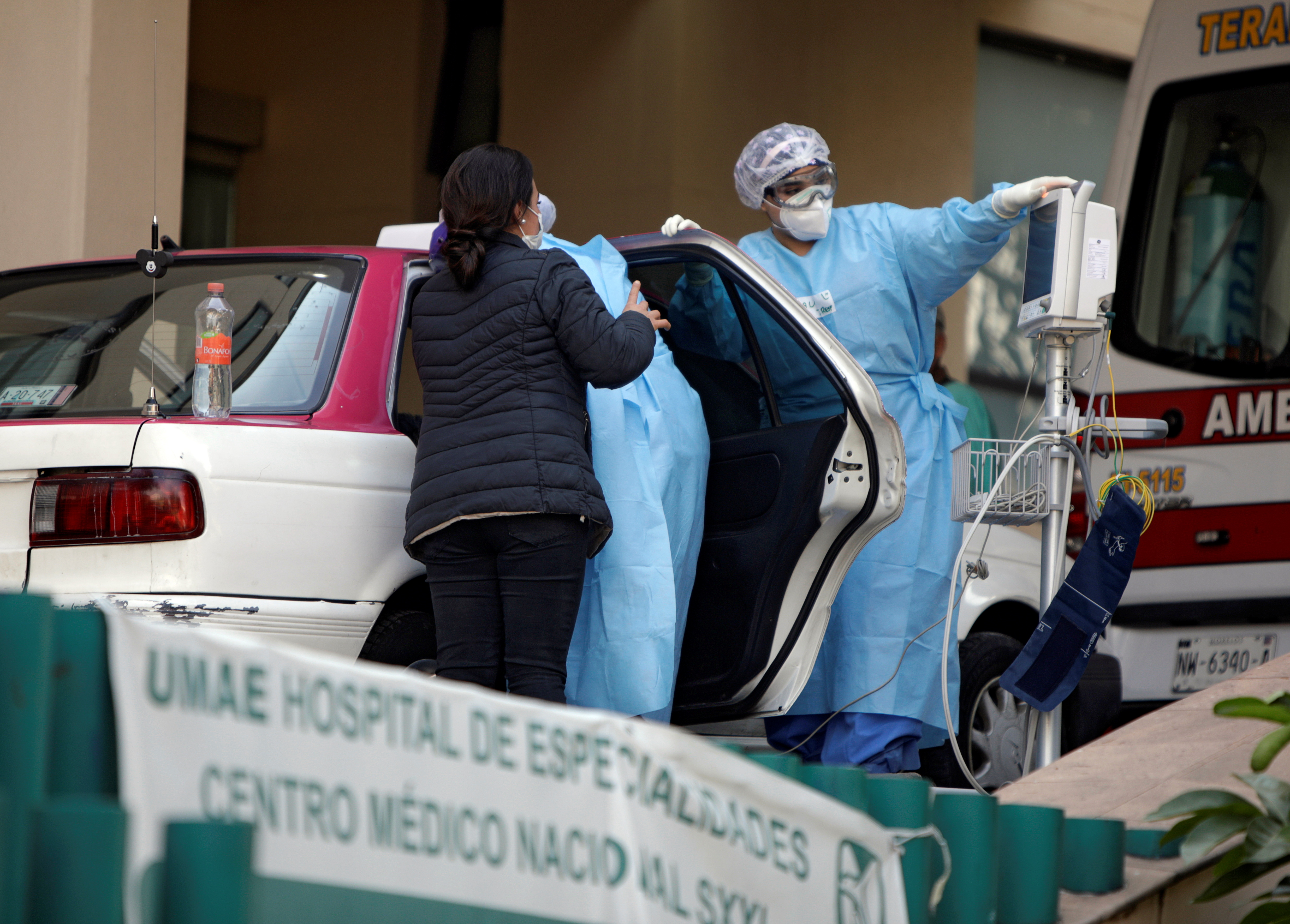 Health workers try to assist an unresponsive man showing symptoms of the coronavirus disease (COVID-19) who was brought to the General Hospital in a taxi, in Mexico City, Mexico January 7, 2021. REUTERS/Luis Cortes