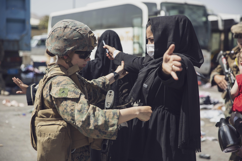 A U.S. Marine checks a woman as she goes through the Evacuation Control Center (ECC) during an evacuation at Hamid Karzai International Airport, Kabul, Afghanistan, August 28, 2021.  U.S. Marine Corps/Staff Sgt. Victor Mancilla/Handout via REUTERS
