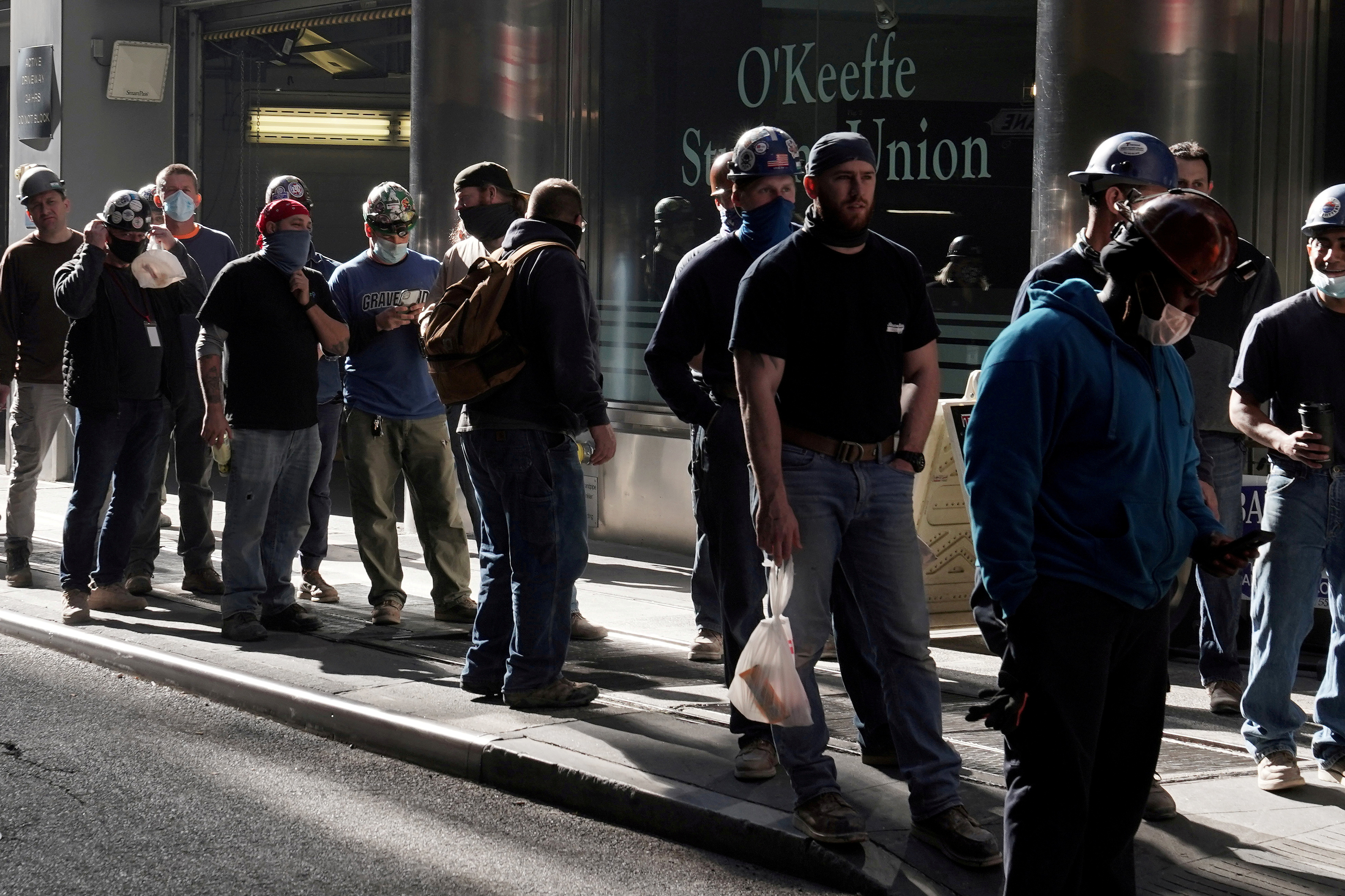 Construction workers wait in line to do a temperature test to return to the job site after lunch, amid the coronavirus disease (COVID-19) outbreak, in the Manhattan borough of New York City, New York, U.S., November 10, 2020. REUTERS/Carlo Allegri/File Photo/File Photo