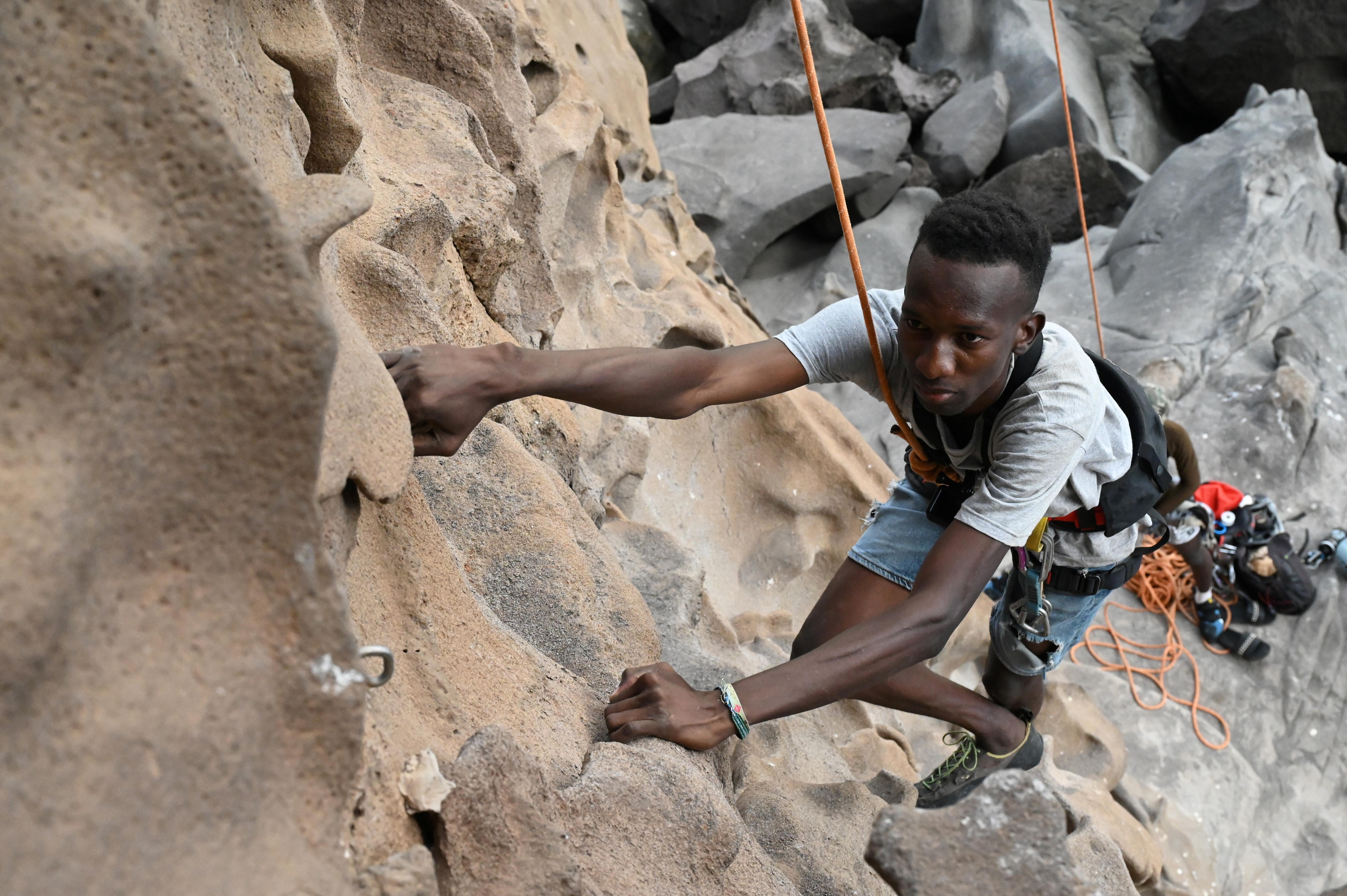 Senegalese rock climber Daouda Diallo climbs a rock wall at the Mamelles cliffs in Dakar, Senegal, July 4, 2021.   REUTERS/Cooper Inveen