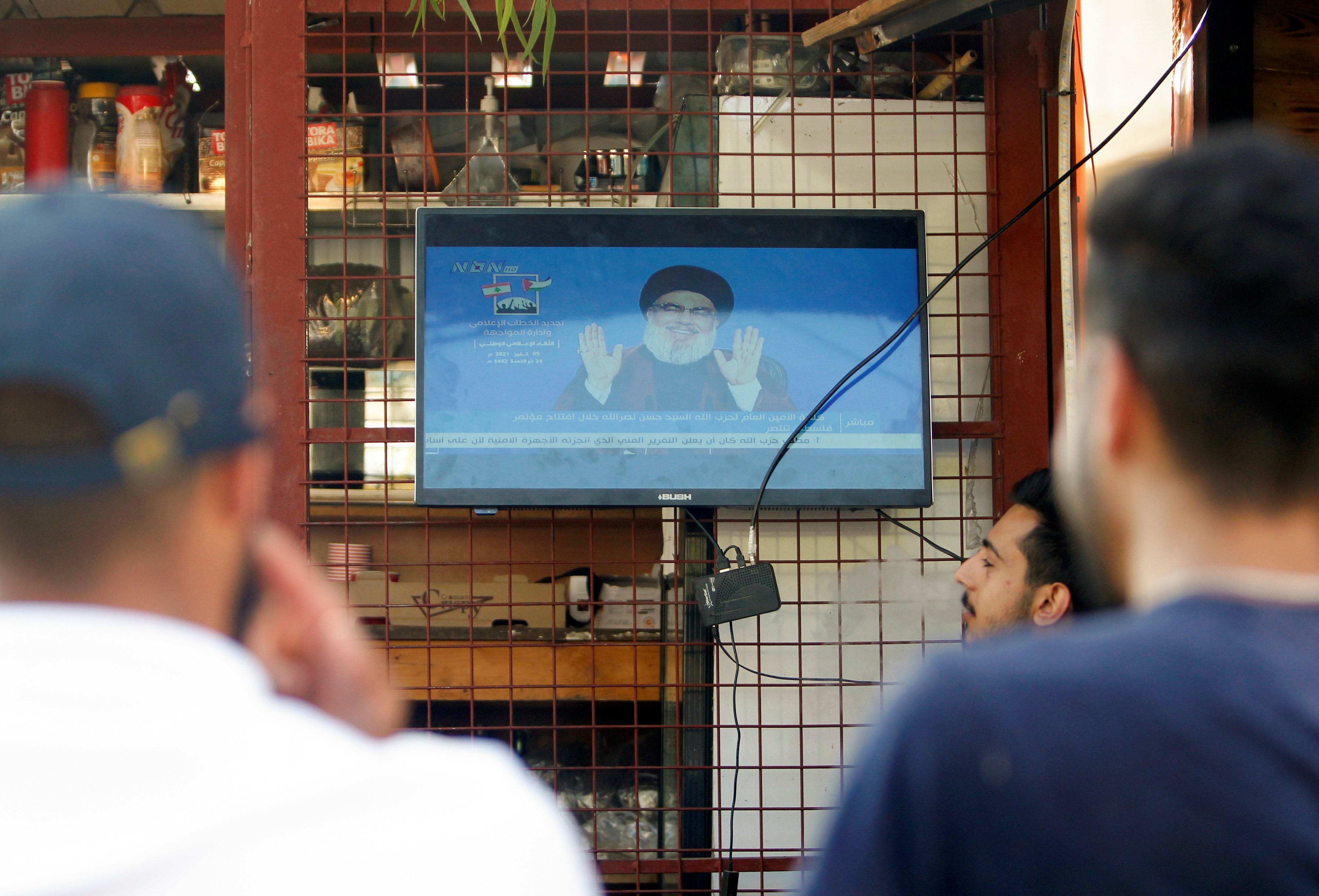 People watch Lebanon's Hezbollah leader Sayyed Hassan Nasrallah speak on television during an event in solidarity with Palestinians, in Houla, Lebanon July 5, 2021. REUTERS/Aziz Taher