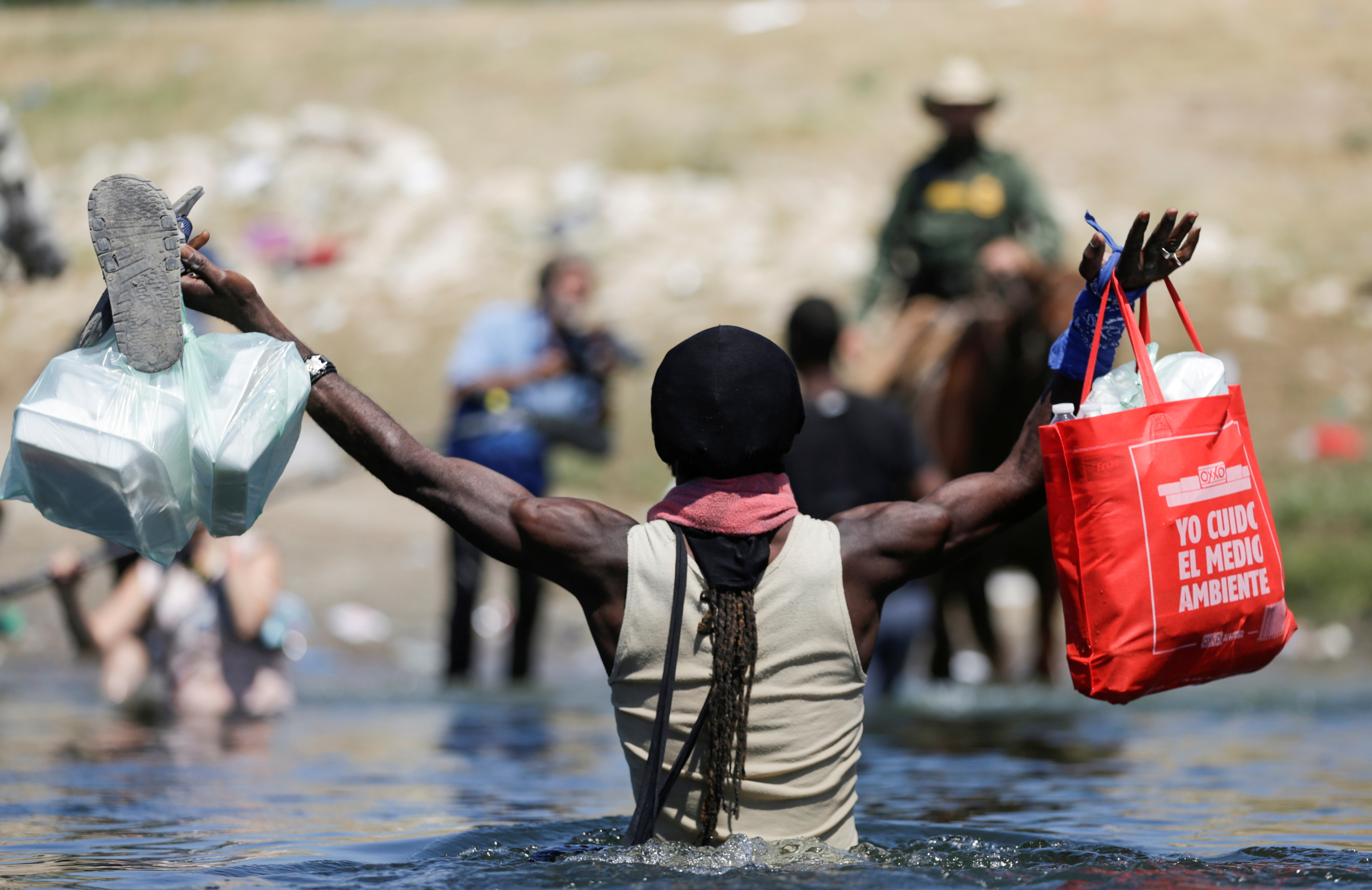 A migrant man asylum seeker walks through the Rio Grande river to cross the border between Ciudad Acuna, Mexico and Del Rio, Texas, U.S., after buying supplies at the Mexican side, in Ciudad Acuna, Mexico September 19, 2021. REUTERS/Daniel Becerril