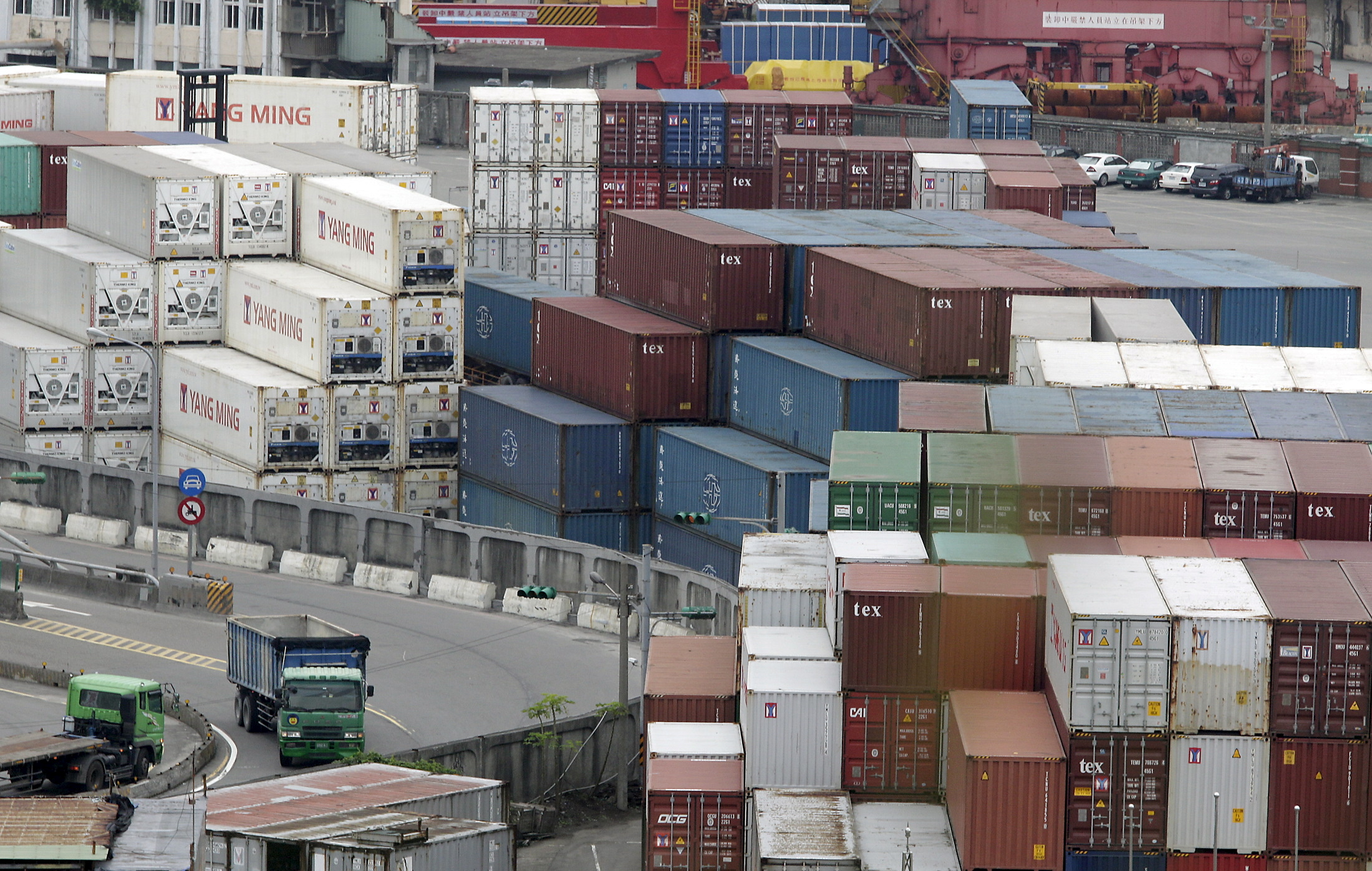 Trucks drive near containers at Keelung port, northern Taiwan, October 30, 2015. REUTERS/Pichi Chuang/File Photo