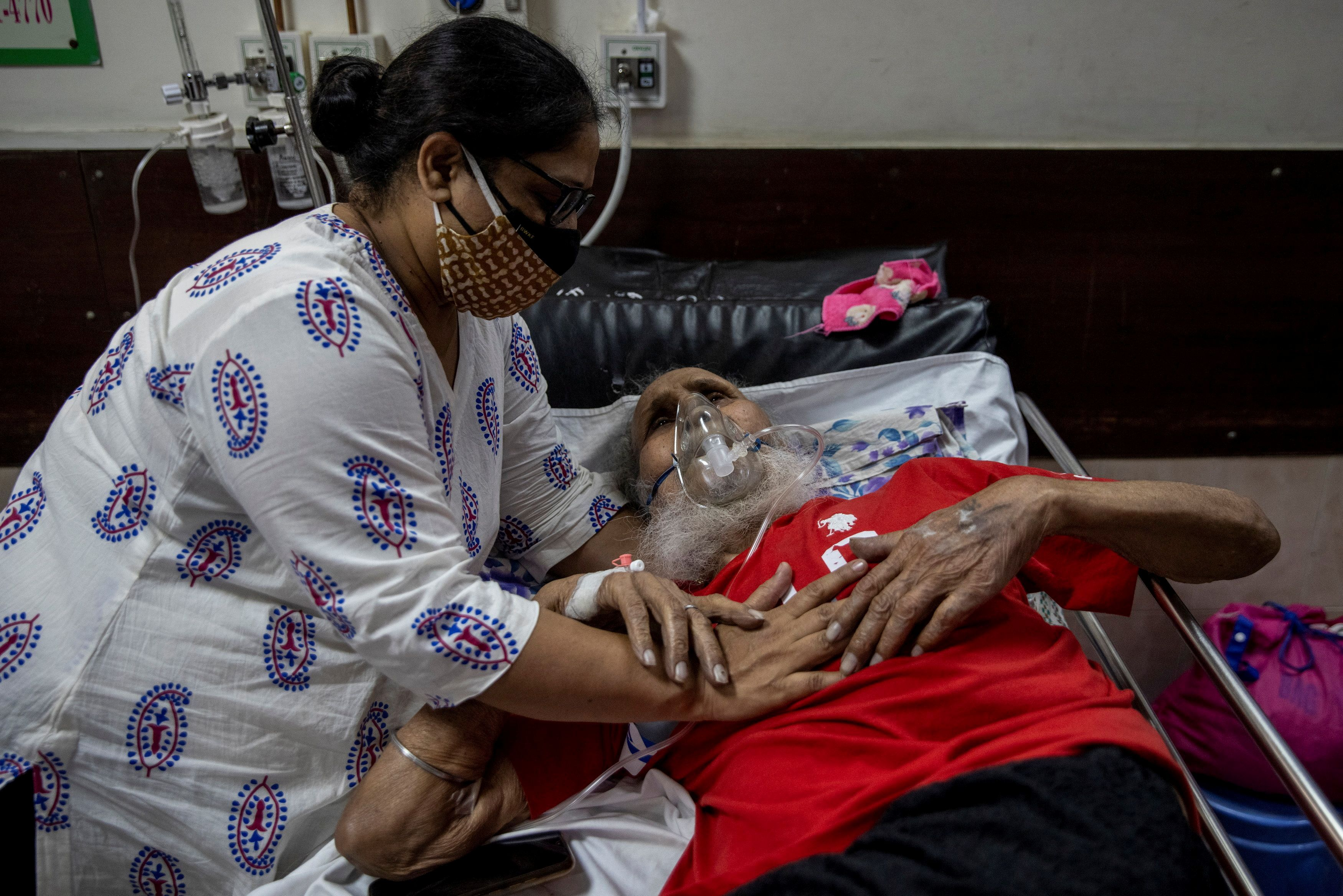 A man suffering from the coronavirus disease (COVID-19) is comforted by his daughter as he receives treatment inside the casualty ward at a hospital in New Delhi, India, May 1, 2021. REUTERS/Danish Siddiqui