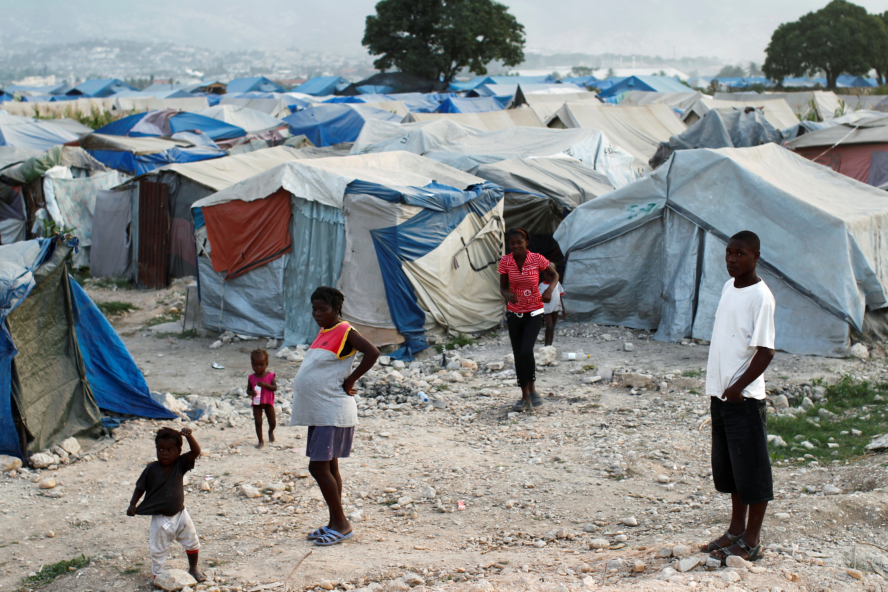 Haitians made homeless in the 2010 earthquake stand outside their tents on the outskirts of Port-au-Prince January 13, 2011. REUTERS/Jorge Silva/File Photo