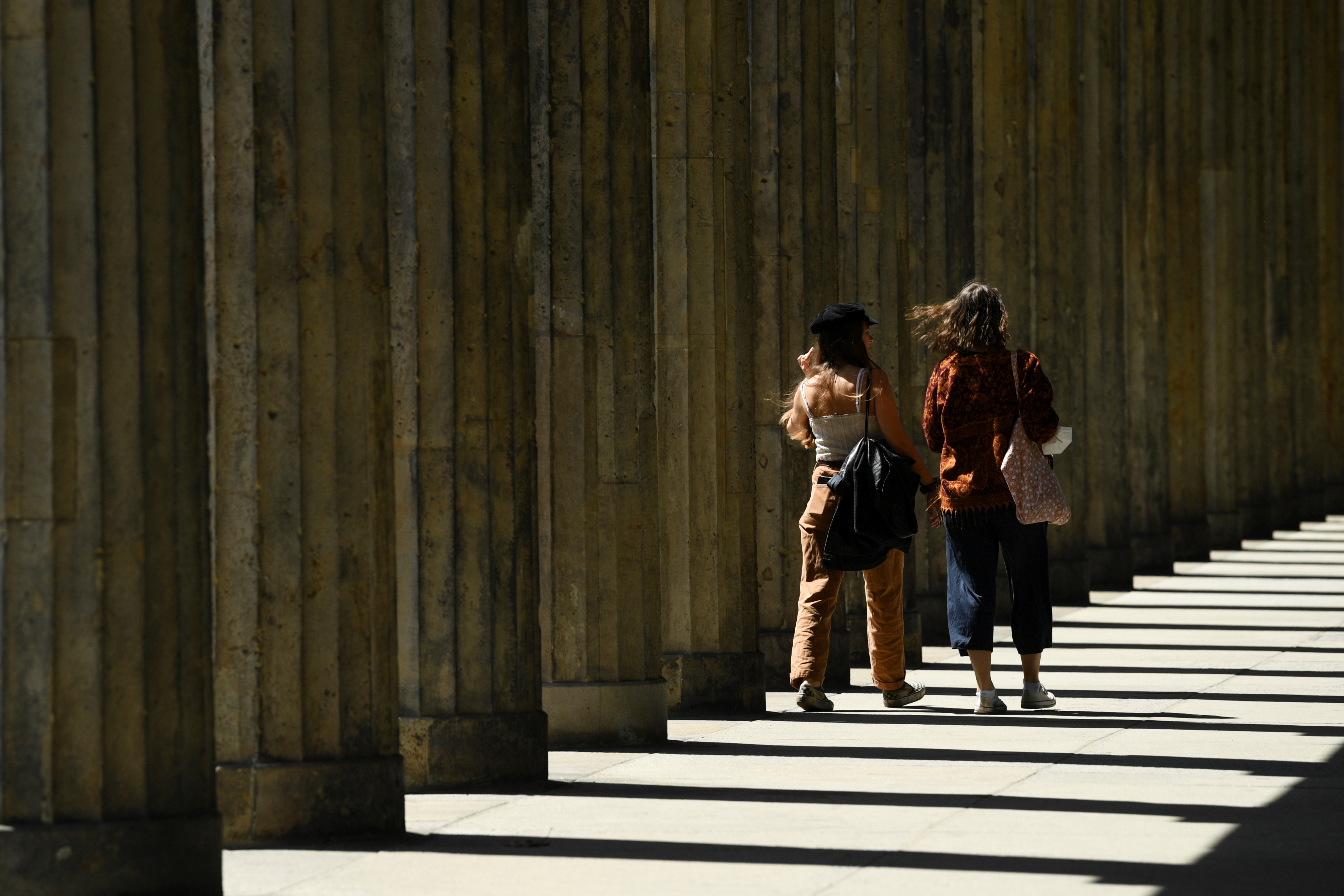 People walk past a colonnade on Museum Island during warm temperatures, amid the coronavirus disease (COVID-19) pandemic, in Berlin, Germany May 30, 2021.  REUTERS/Annegret Hilse