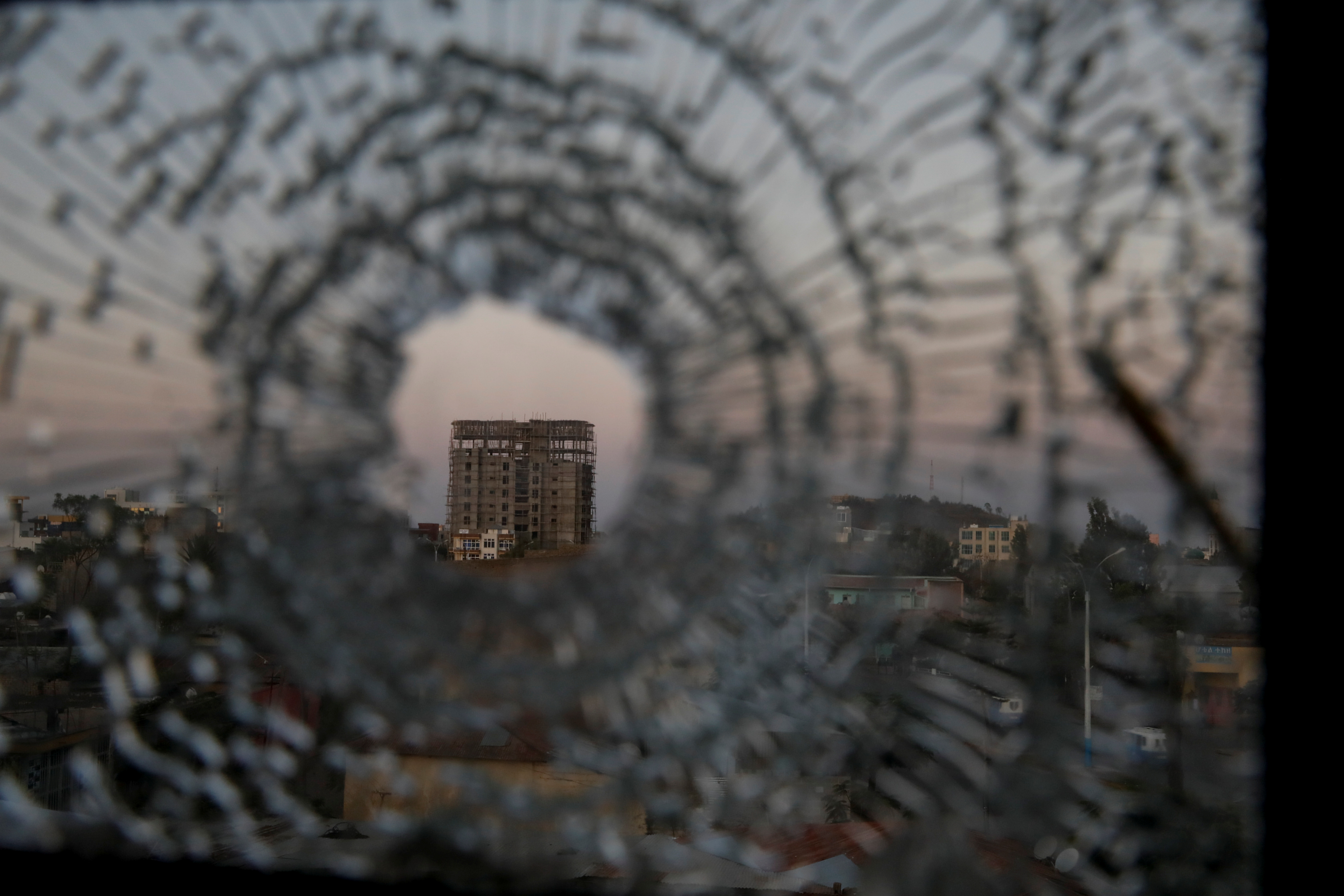 A building is seen through a bullet hole in a window of the Africa Hotel in the town of Shire, Tigray region, Ethiopia, March 17, 2021. REUTERS/Baz Ratner
