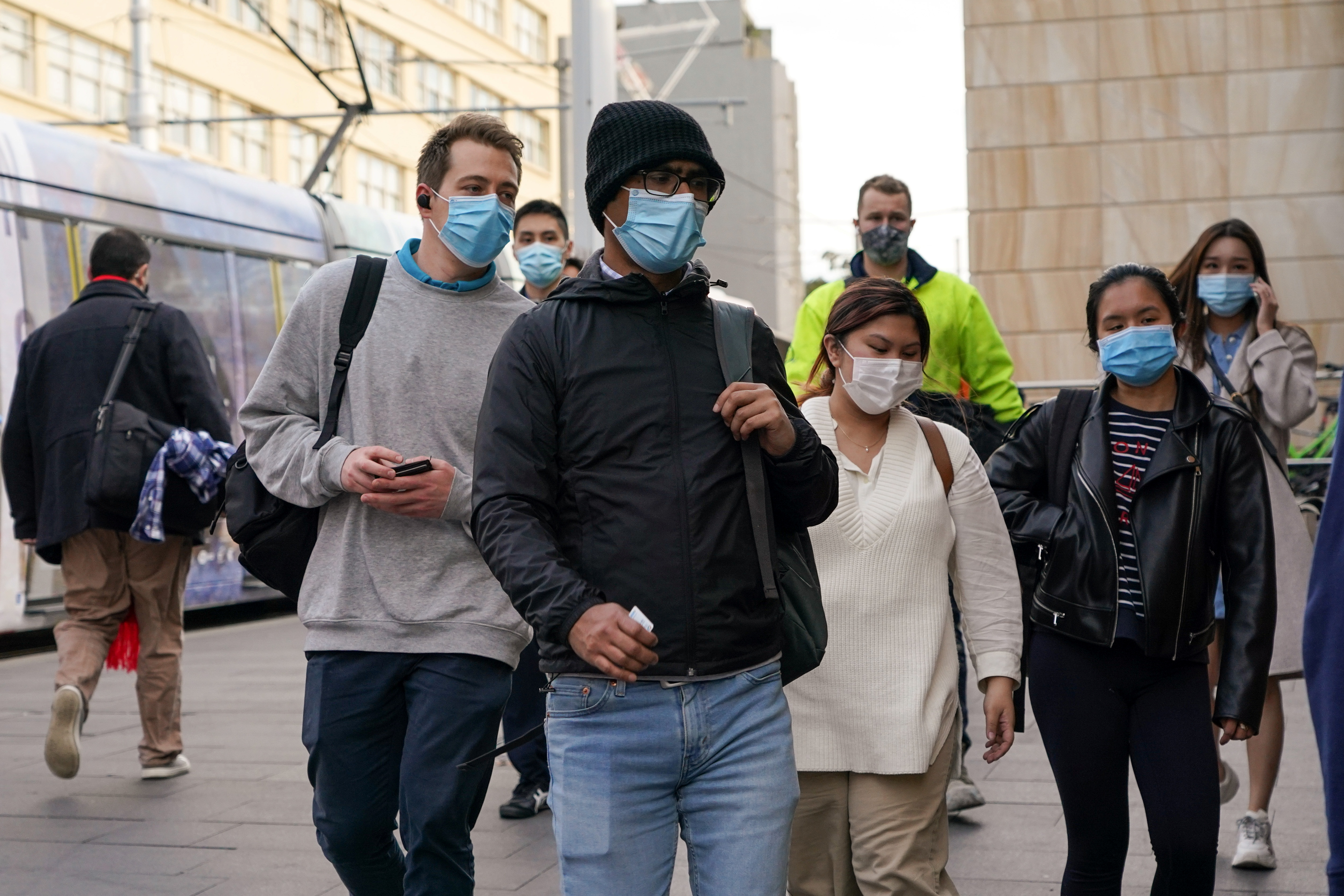 Commuters wear protective face masks as they enter Central Station following the implementation of new public health regulations from the state of New South Wales, as the city grapples with an outbreak of the coronavirus disease (COVID-19) in Sydney, Australia, June 23, 2021.  REUTERS/Loren Elliott