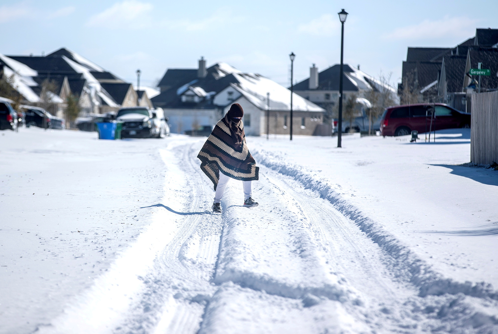 A man walks to his friend's home in a neighbourhood without electricity as snow covers the BlackHawk neighborhood in Pflugerville, Texas, U.S. February 15, 2021. Picture taken February 15, 2021.   Bronte Wittpenn/Austin American-Statesman/USA Today Network via REUTERS//File Photo