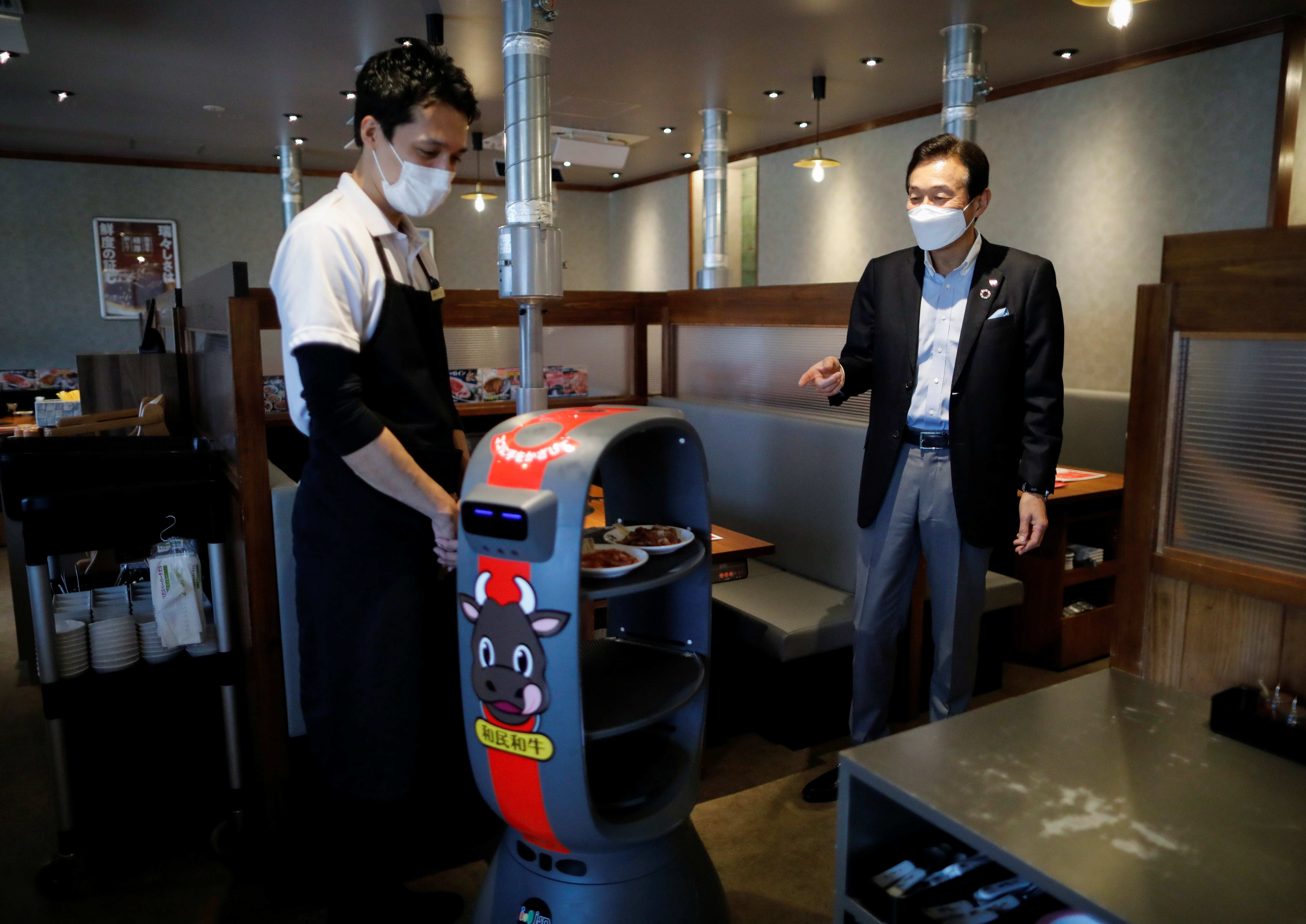 Miki Watanabe, Chairman and CEO of Watami Co. talks with a staff member next to a serving robot at their yakiniku barbecue restaurant named 'Yakiniku no Watami', in Tokyo, Japan September 15, 2021. Picture taken September 15, 2021.  REUTERS/Issei Kato