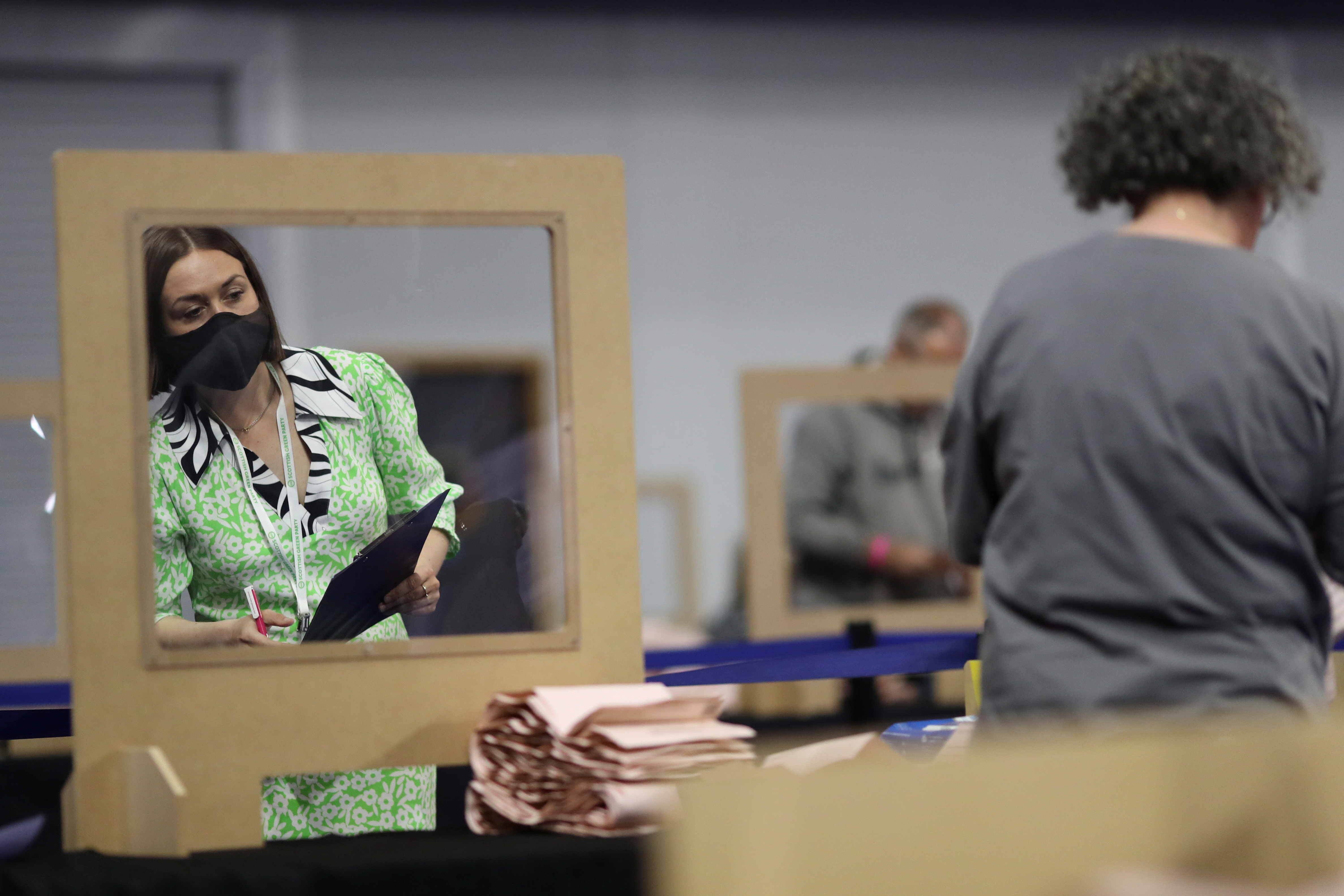 A woman watches as an election staff member counts votes for the Scottish Parliamentary election at a counting centre in Glasgow, Scotland, Britain, May 8, 2021. REUTERS/Russell Cheyne