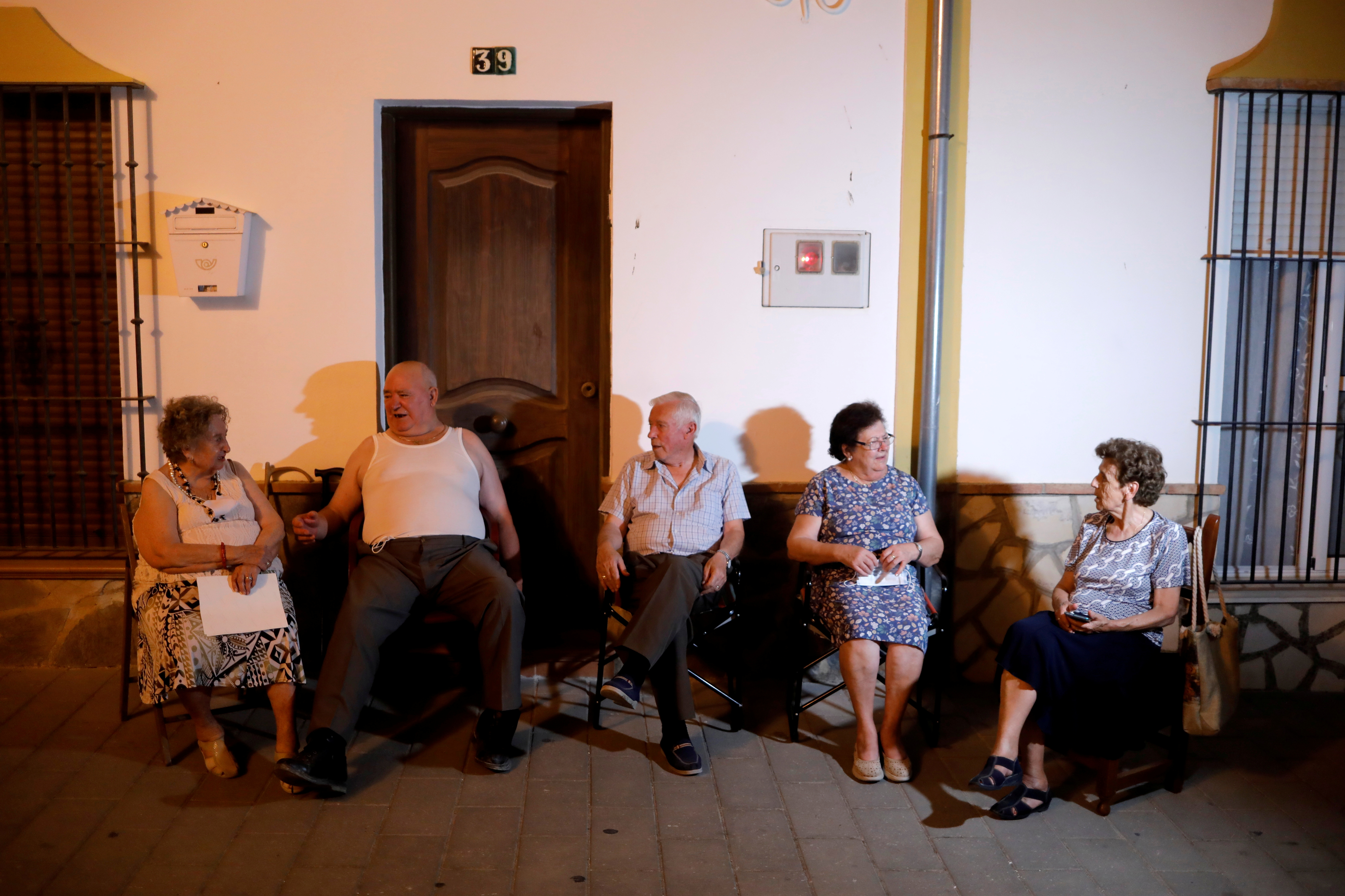 Neighbours chat outside their houses to avoid the heat at night, as a heatwave hits Spain, in Algar, August 12, 2021.  REUTERS/Jon Nazca