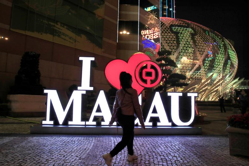 A woman walks past a Bank of China branch next to the Grand Lisboa hotel and casino (R) in Macau, China December 21, 2019. REUTERS/Jason Lee
