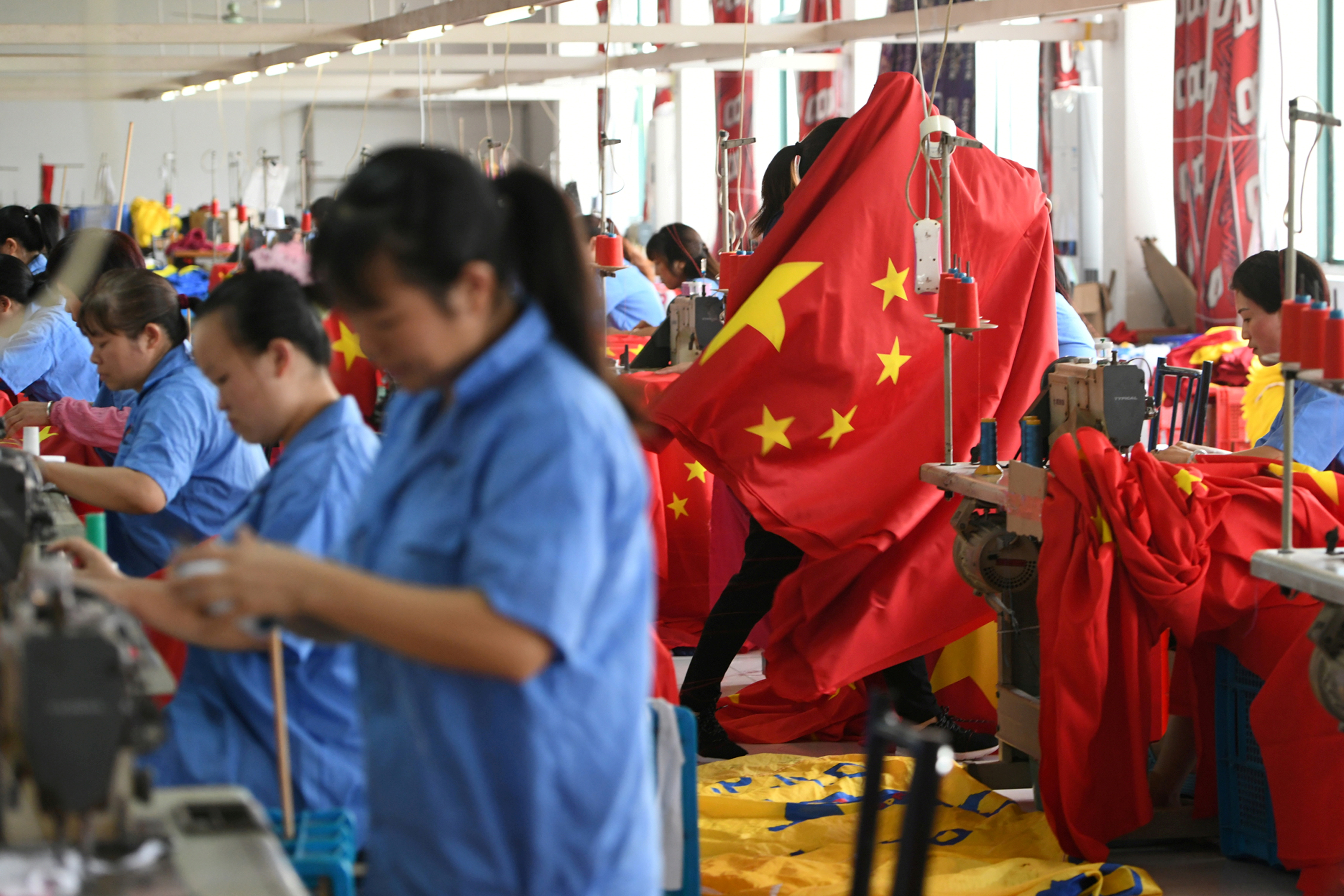 Workers make Chinese flags at a factory in Jiaxing, Zhejiang province, China September 25, 2019. REUTERS/Stringer/File Photo