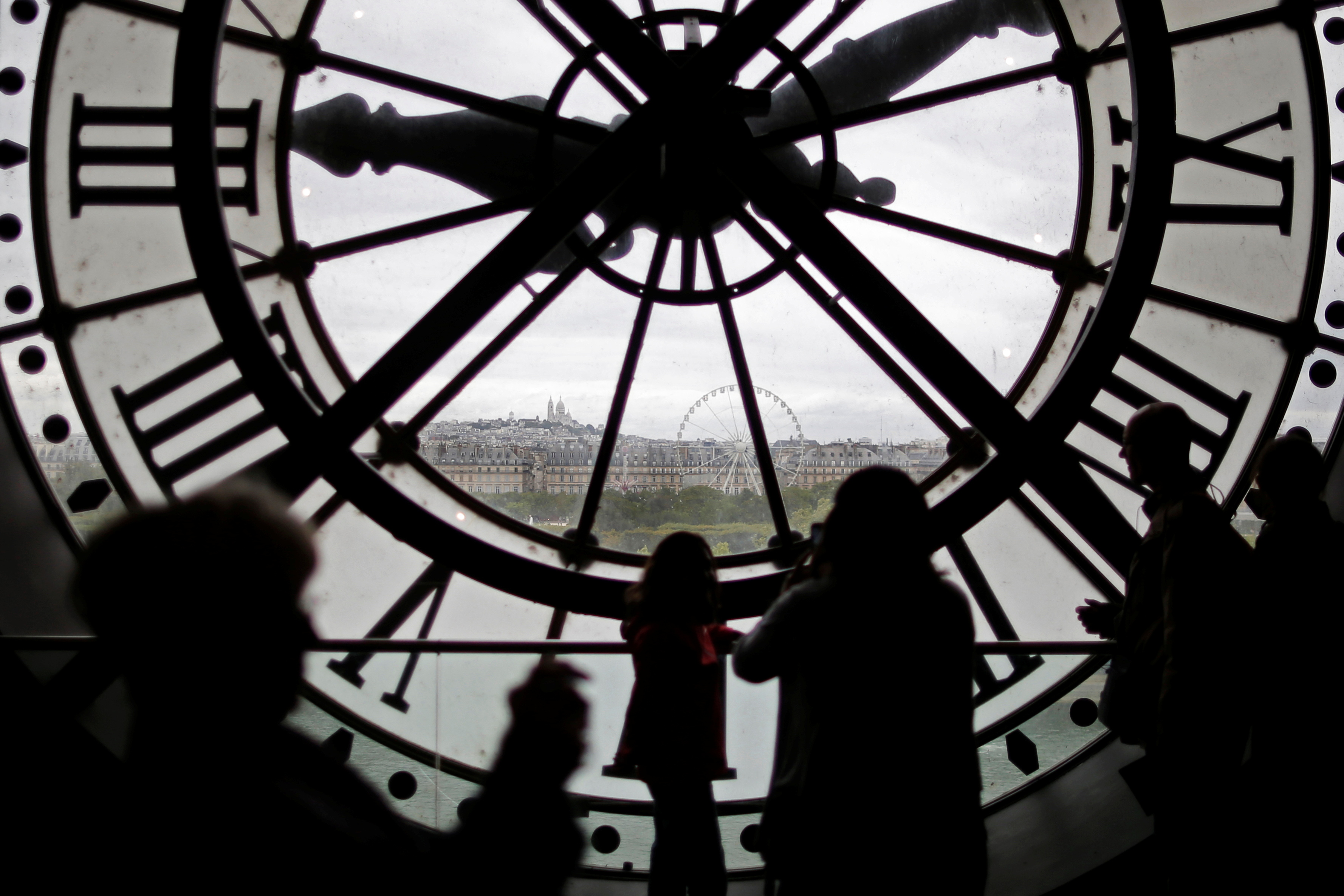 Visitors at the Musee d'Orsay are seen in silhouette as they look behind a giant clock face at the former Orsay railway station, in Paris, France, July 28, 2015. REUTERS/Stephane Mahe/File Photo