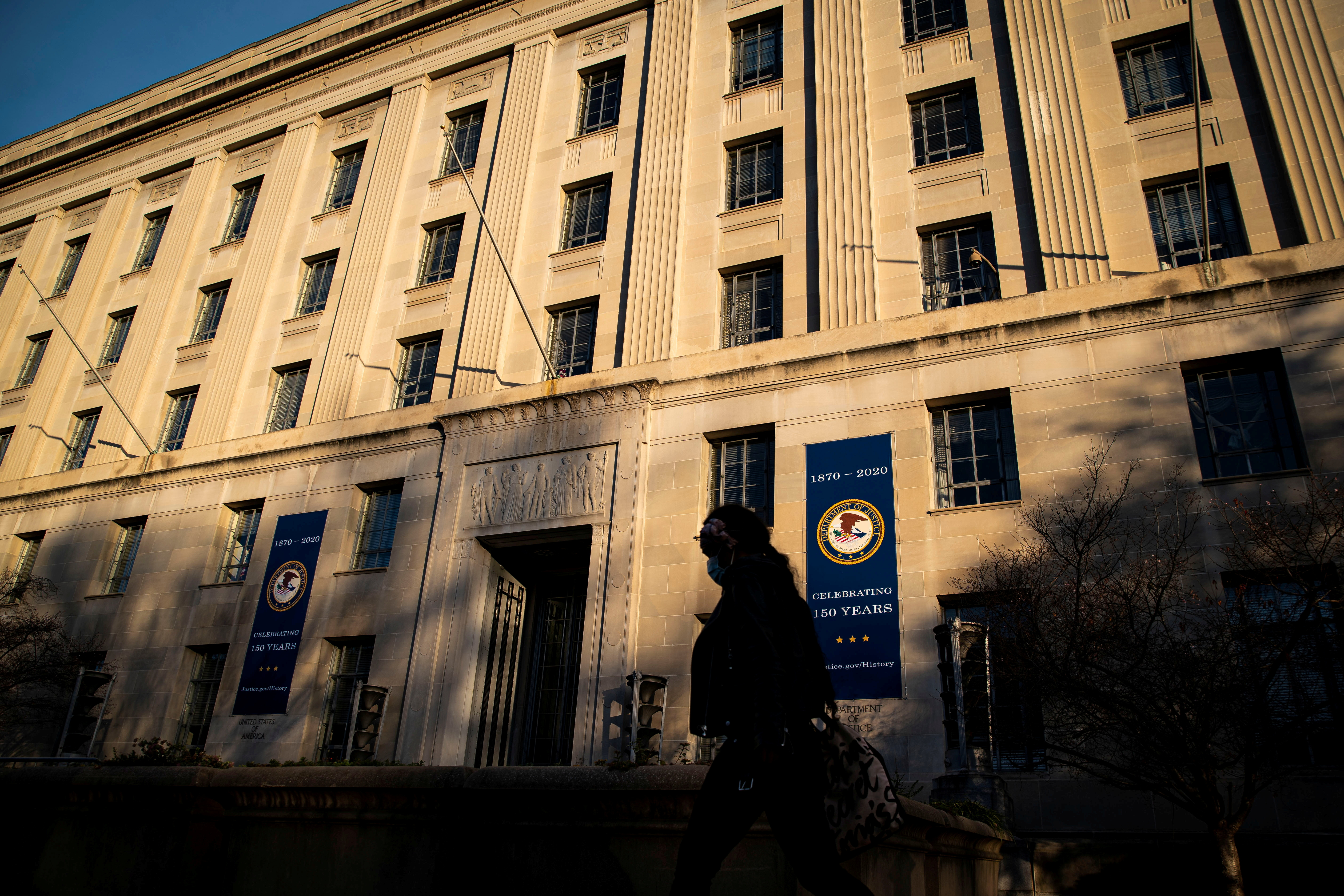 A woman walks past the U.S. Department of Justice Building, in Washington, U.S., December 15, 2020. REUTERS/Al Drago