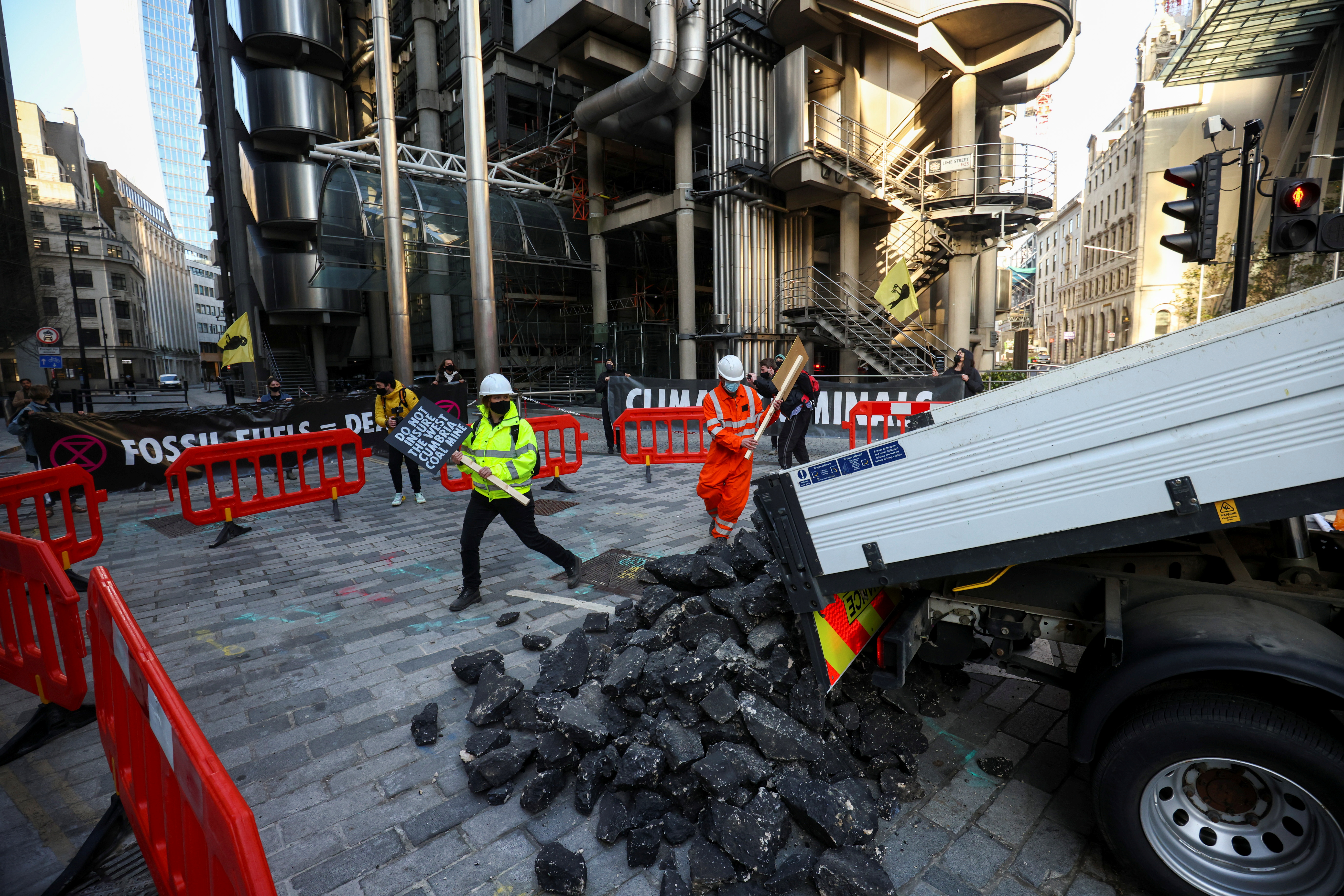 Activists from Extinction Rebellion, a global environmental movement, hold placards as they unload fake coal, made from rocks, from a truck onto the street, during a protest outside the Lloyd's building in London, Britain April 23, 2021. REUTERS/Henry Nicholls