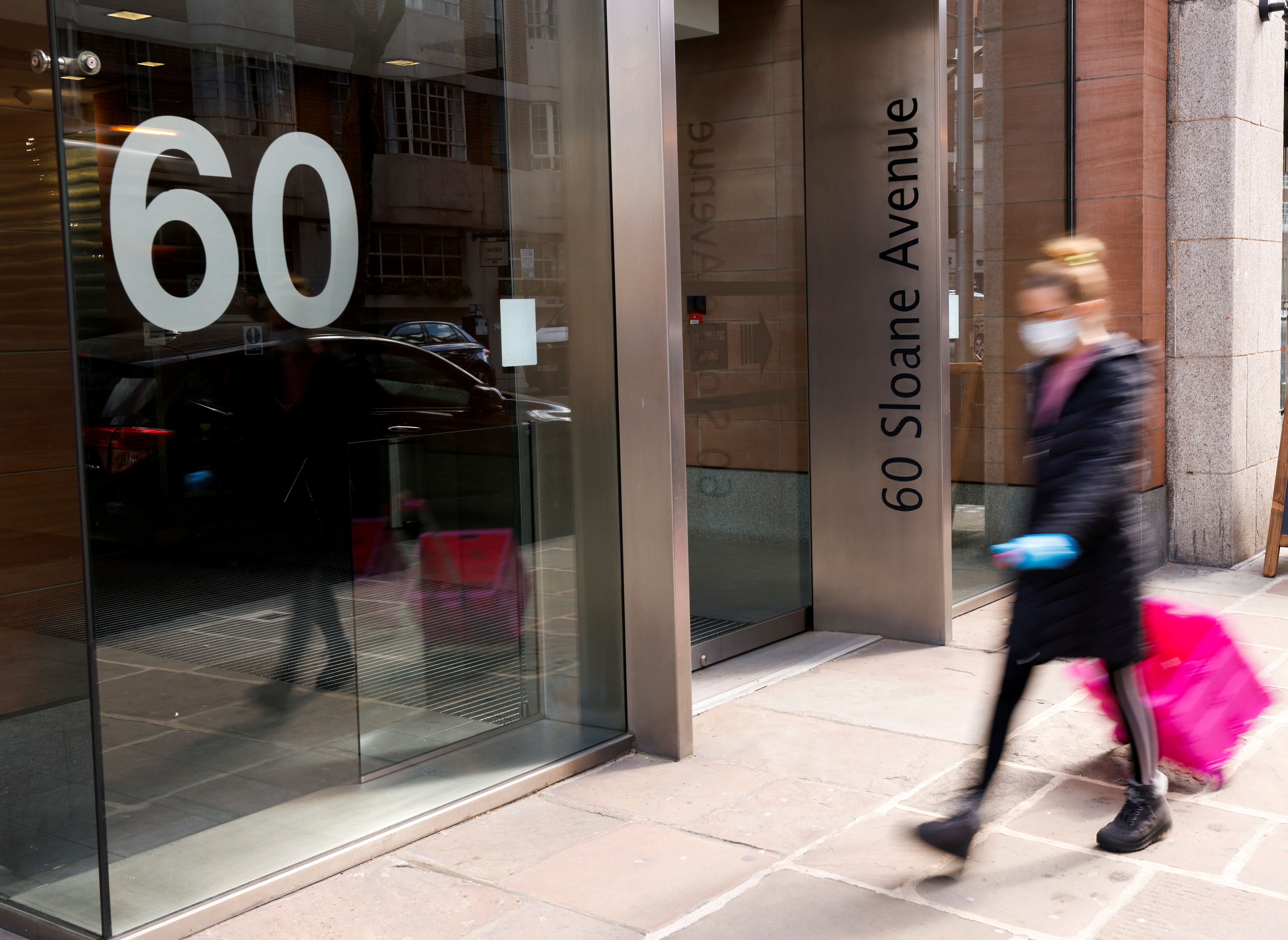 A woman walks past the entrance to the 60 Sloane Avenue in London, Britain, April 13, 2021. REUTERS/John Sibley