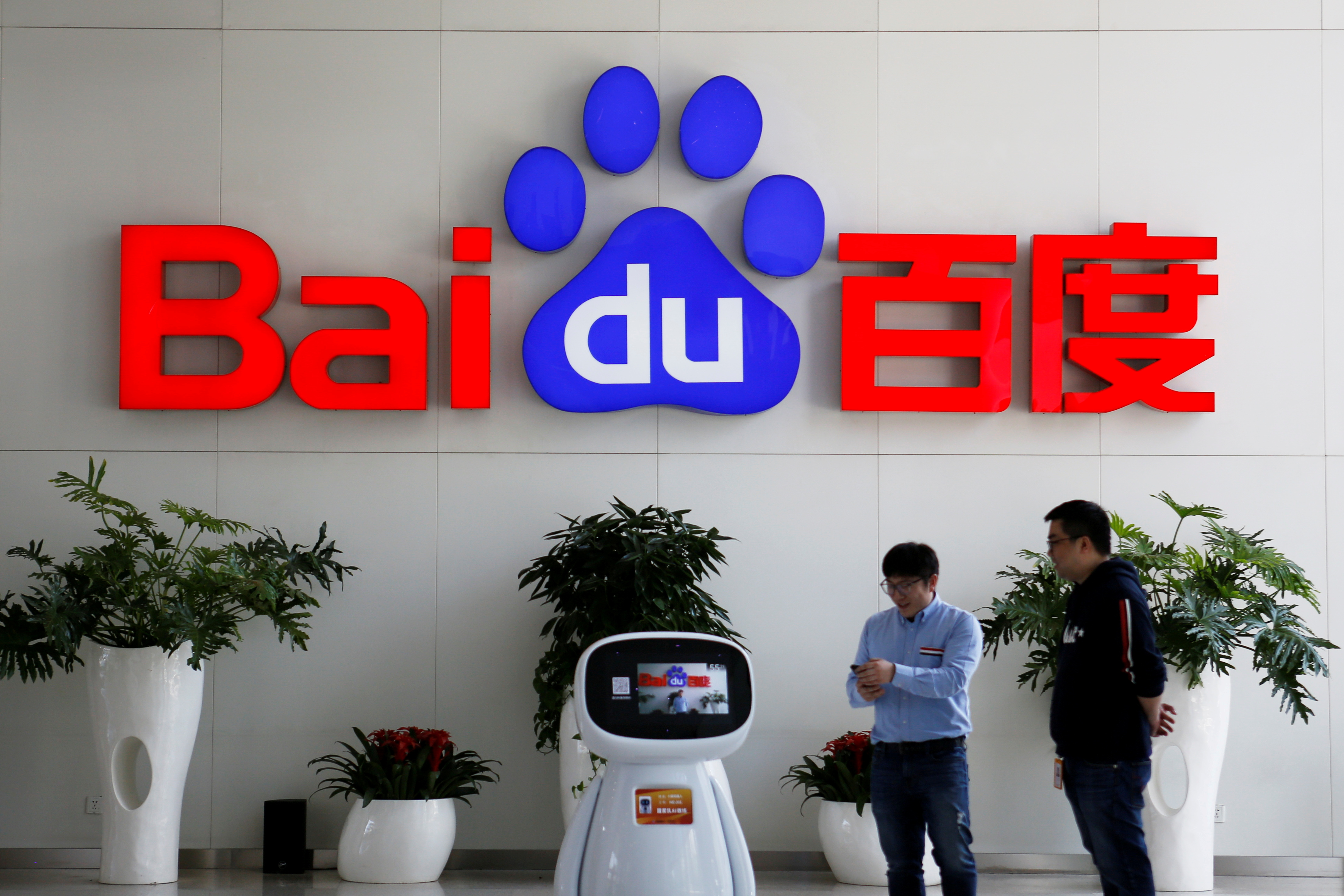 Men interact with a Baidu AI robot near the company logo at its headquarters in Beijing, China April 23, 2021. REUTERS/Florence Lo/File Photo