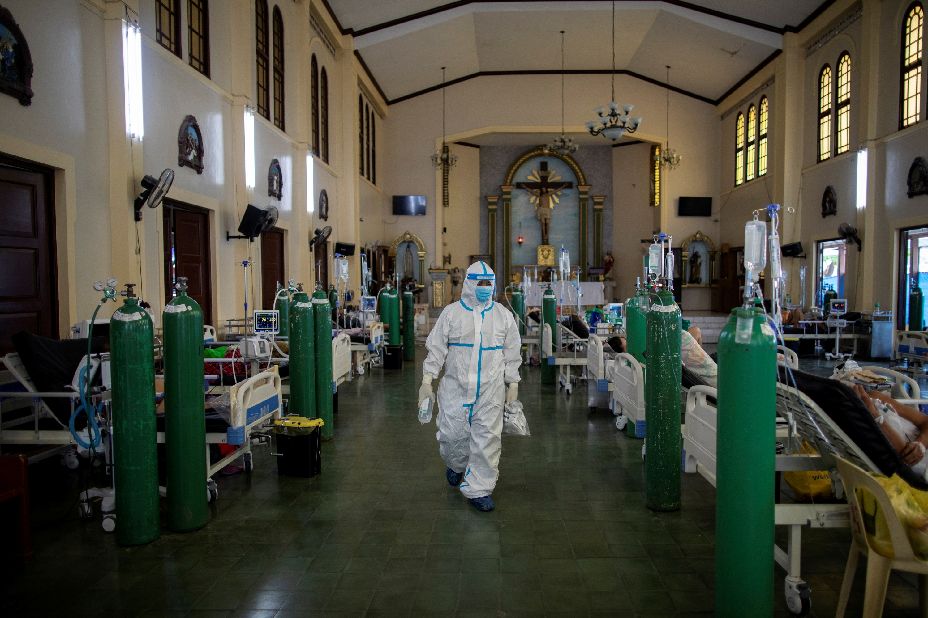 A health worker walks around to check on coronavirus disease (COVID-19) patients admitted in the chapel of Quezon City General Hospital turned into a COVID-19 ward amid rising infections, in Quezon City, Metro Manila, Philippines, August 20, 2021. REUTERS/Eloisa Lopez