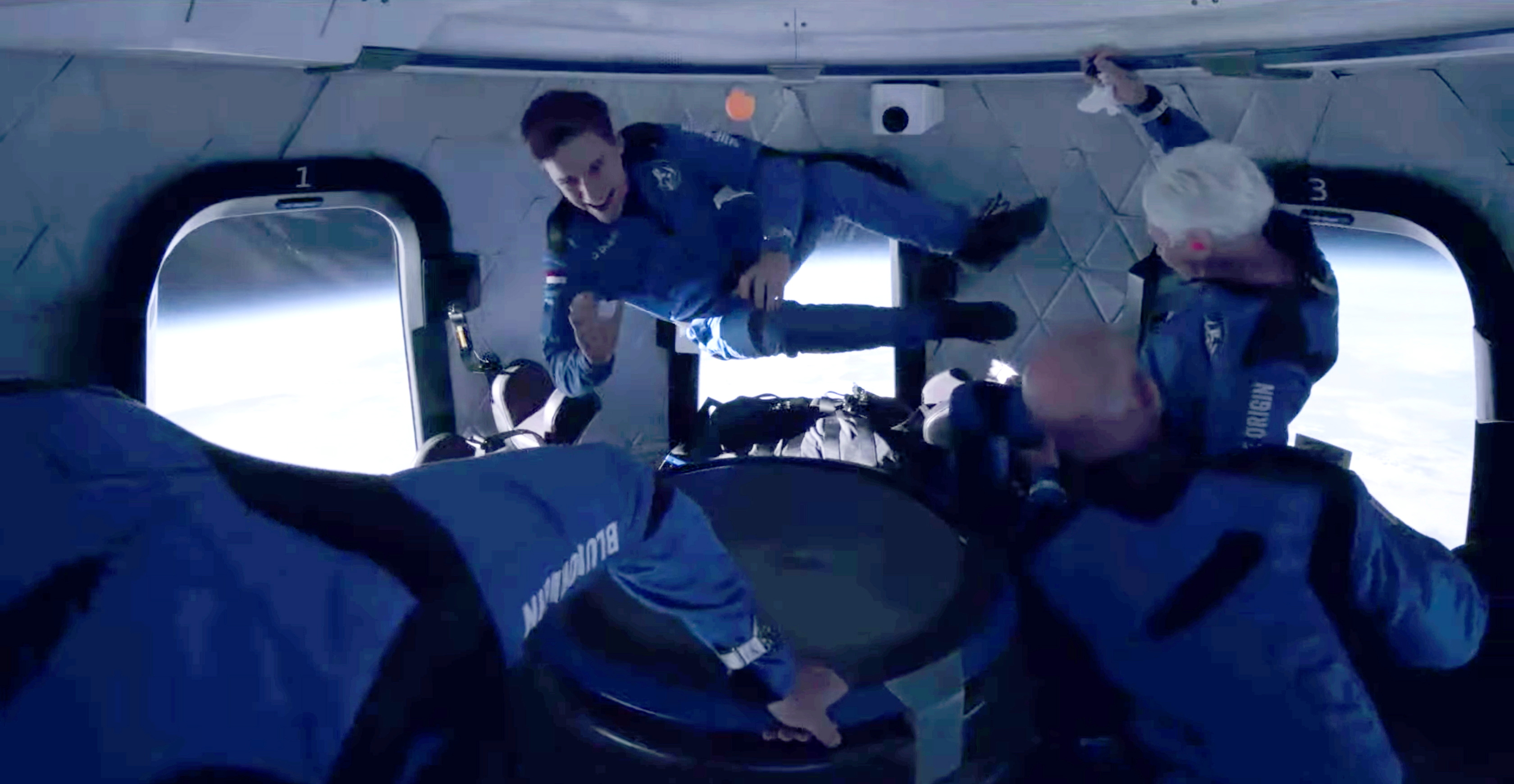Recent Dutch high school graduate Oliver Daemen and pioneering female aviator Wally Funk float weightlessly in their capsule with billionaire businessman Jeff Bezos and his brother Mark after ascending in sub-orbital flight aboard Blue Origin's New Shepard rocket over Van Horn, Texas, U.S., July 20, 2021 in a still image from video.  Blue Origin/Handout via REUTERS.