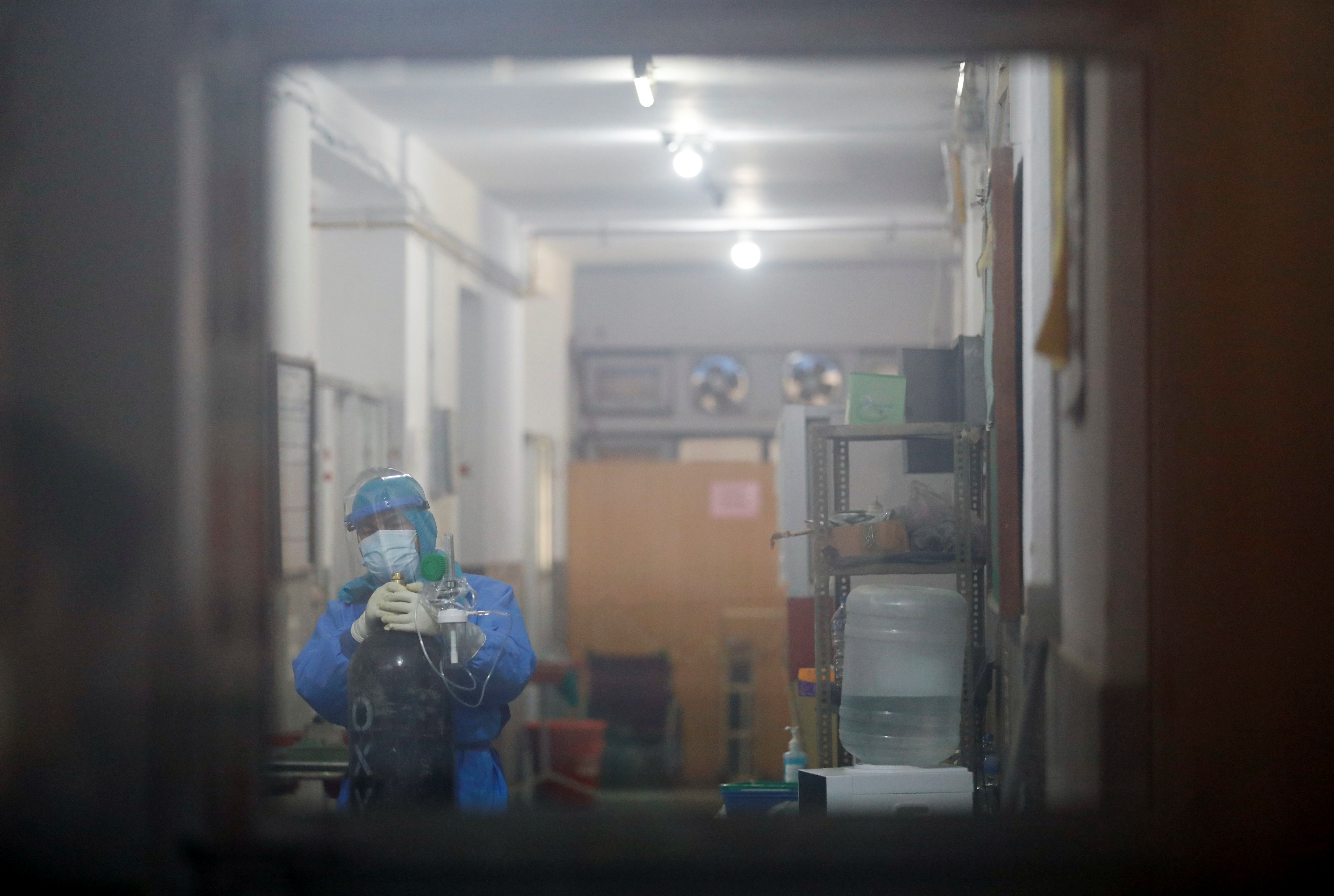 A health worker wearing personal protective equipment (PPE) is seen through the window as he drags an oxygen cylinder towards the COVID ward as the major second wave of the coronavirus disease (COVID-19) surges in Kathmandu, Nepal April 26, 2021. REUTERS/Navesh Chitrakar